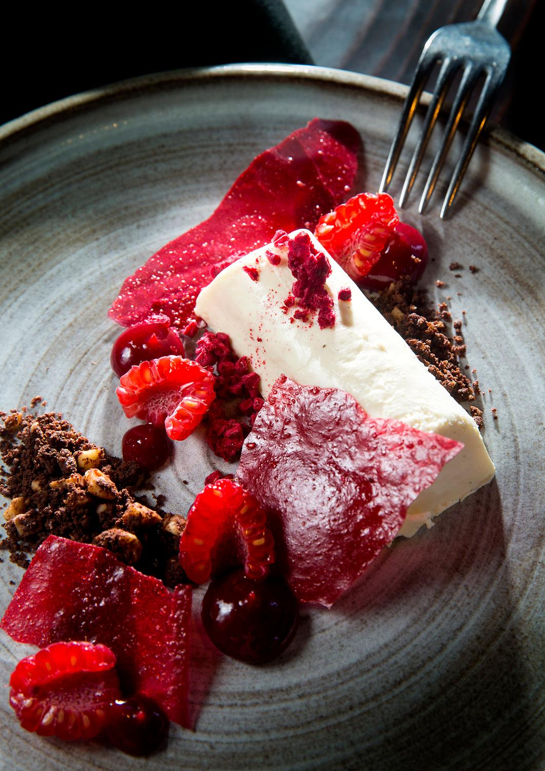 The Vanilla Cheesecake, with raspberry gel, fresh raspberries, and chocolate hazelnut streusel, at Outlier, located at 1101 4th Ave, Seattle. (Sy Bean / Seattle Refined)