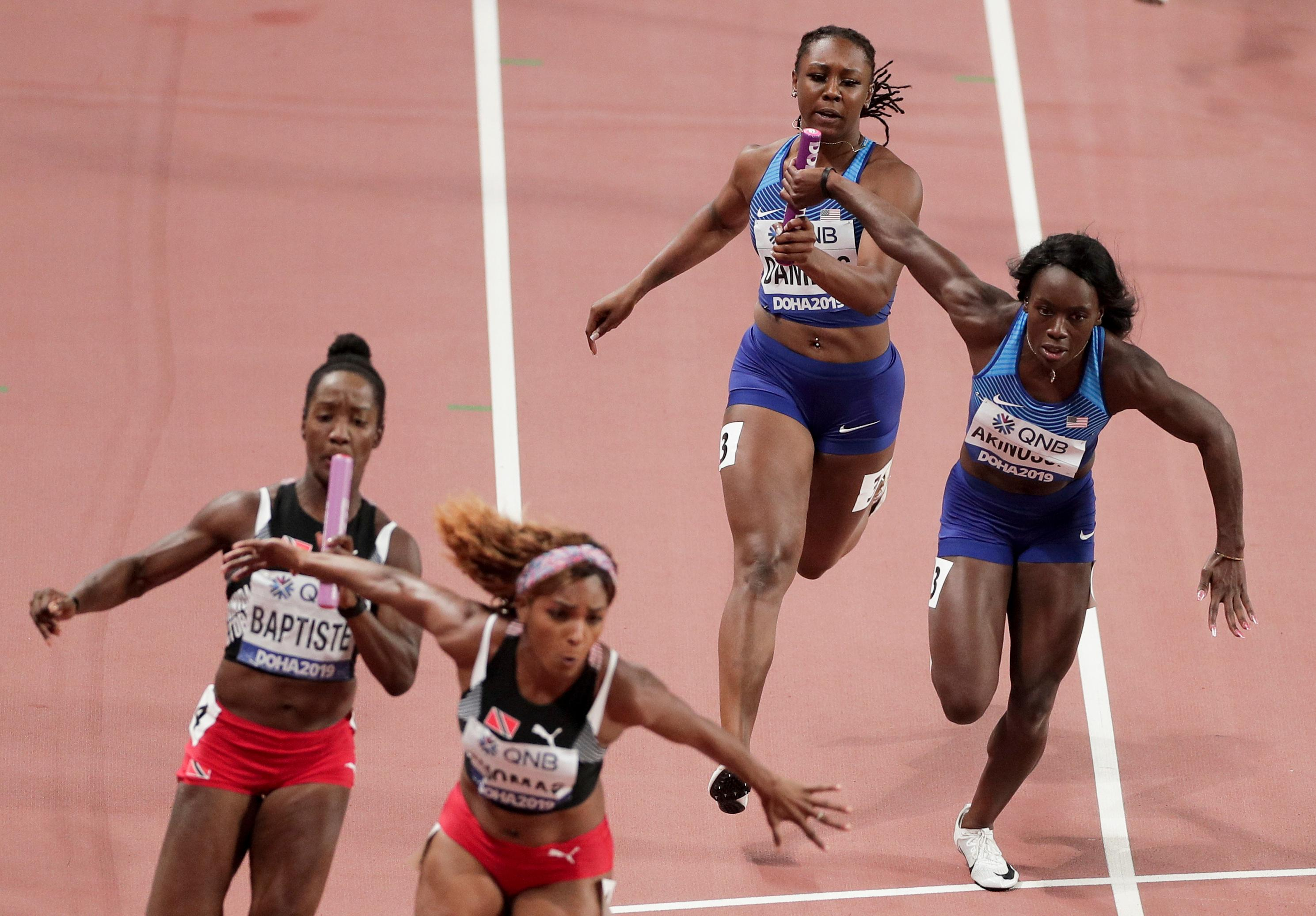 Teahna Daniels, right, of the United States hands off to Morolake Akinosun in the women's 4x100 meter relay semifinal at the World Athletics Championships in Doha, Qatar, Friday, Oct. 4, 2019. (AP Photo/Nariman El-Mofty)