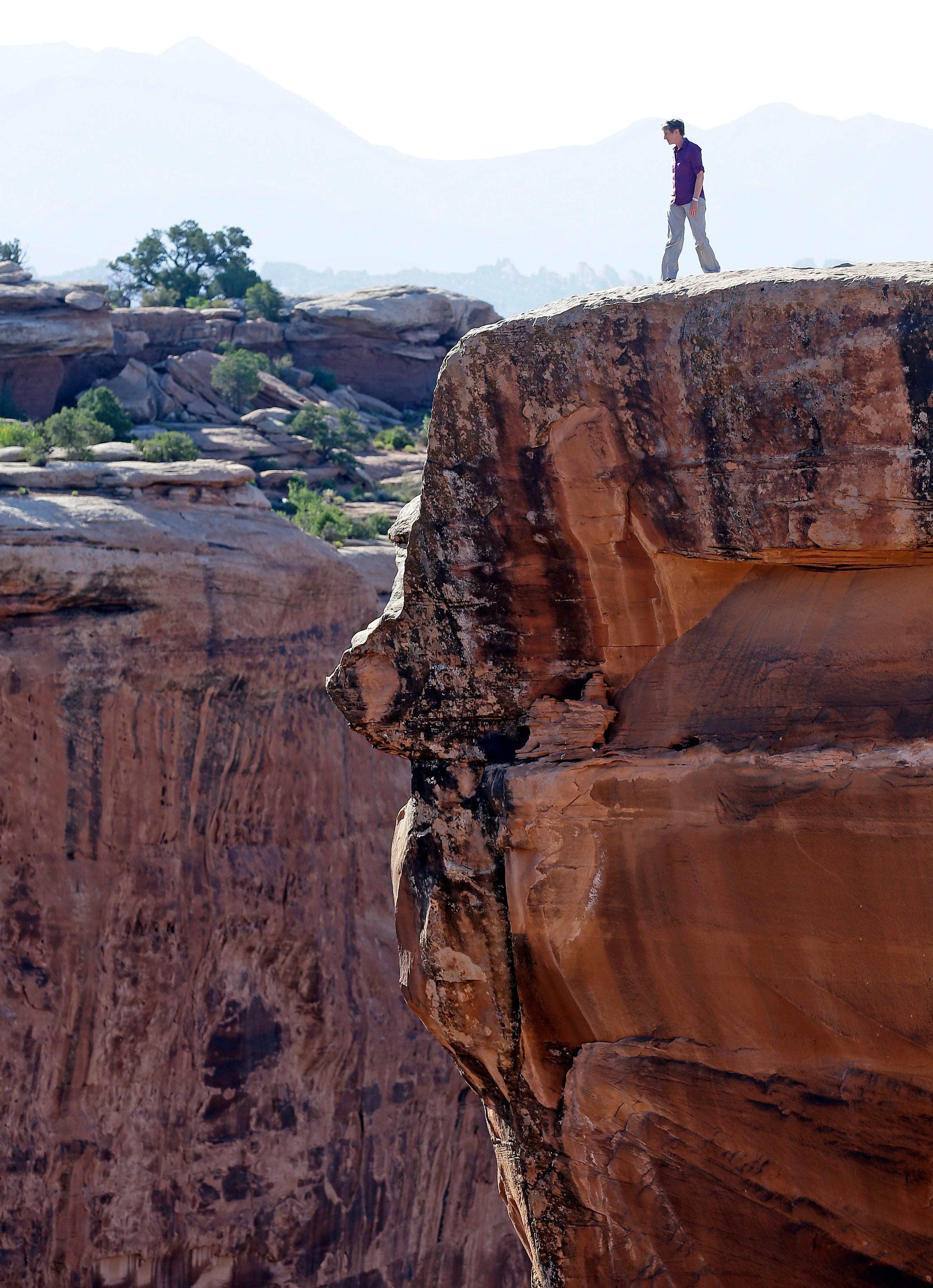 "FILE - In this July 14, 2016 file photo, then-Interior Secretary Sally Jewell looks in to a canyon at Gemini Bridges near Moab, Utah, during a tour to meet with proponents and opponents to the ""Bears Ears"" monument proposal. Interior Secretary Ryan Zinke is recommending that the new Bears Ears National Monument in Utah be reduced in size and says Congress should step in to designate how selected areas of the 1.3 million-acre site are categorized. (AP Photo/Rick Bowmer, File)   Interior Secretary Ryan Zinke is recommending that the new Bears Ears National Monument in Utah be reduced in size and says Congress should step in to designate how selected areas of the 1.3 million-acre site are categorized."