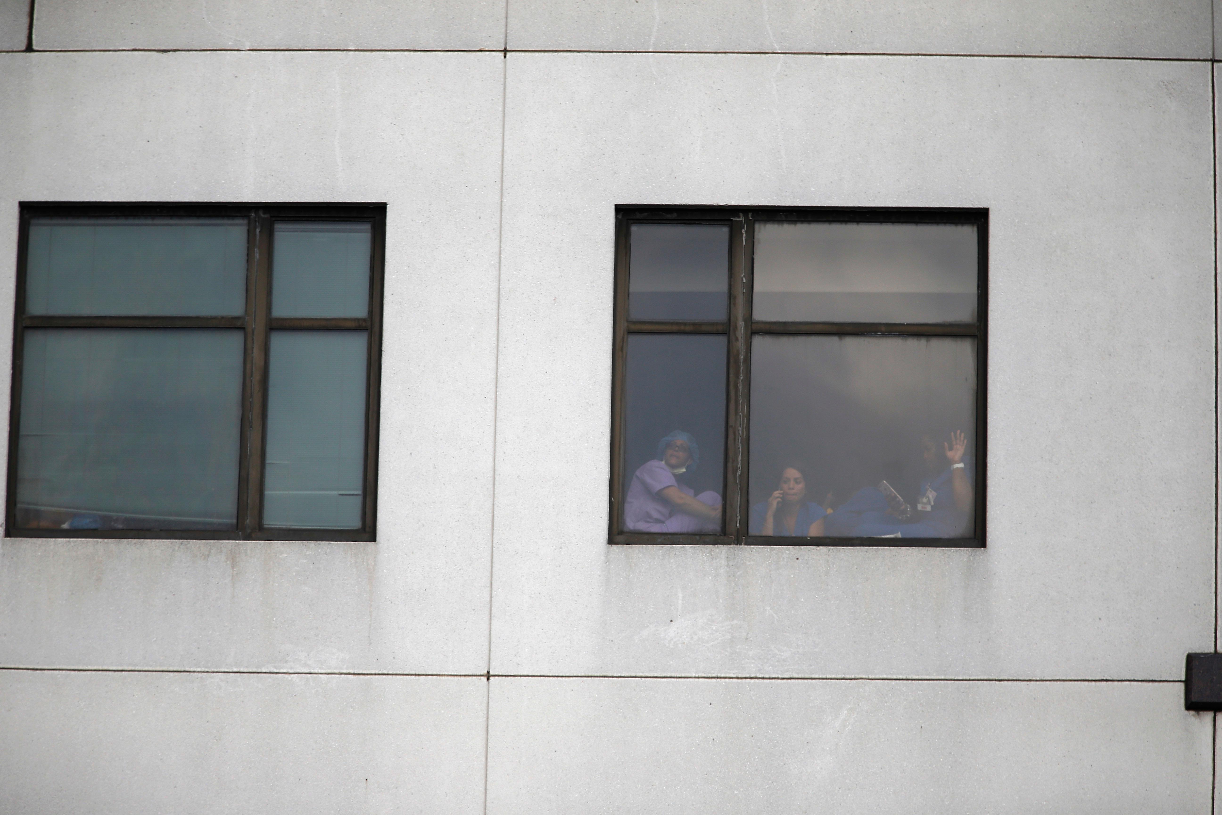 Those still inside the building peek out the windows after a shooting killing one and wounding six others at Bronx Lebanon Hospital Center Friday, June 30, 2017, in New York. (AP Photo/Michael Noble)
