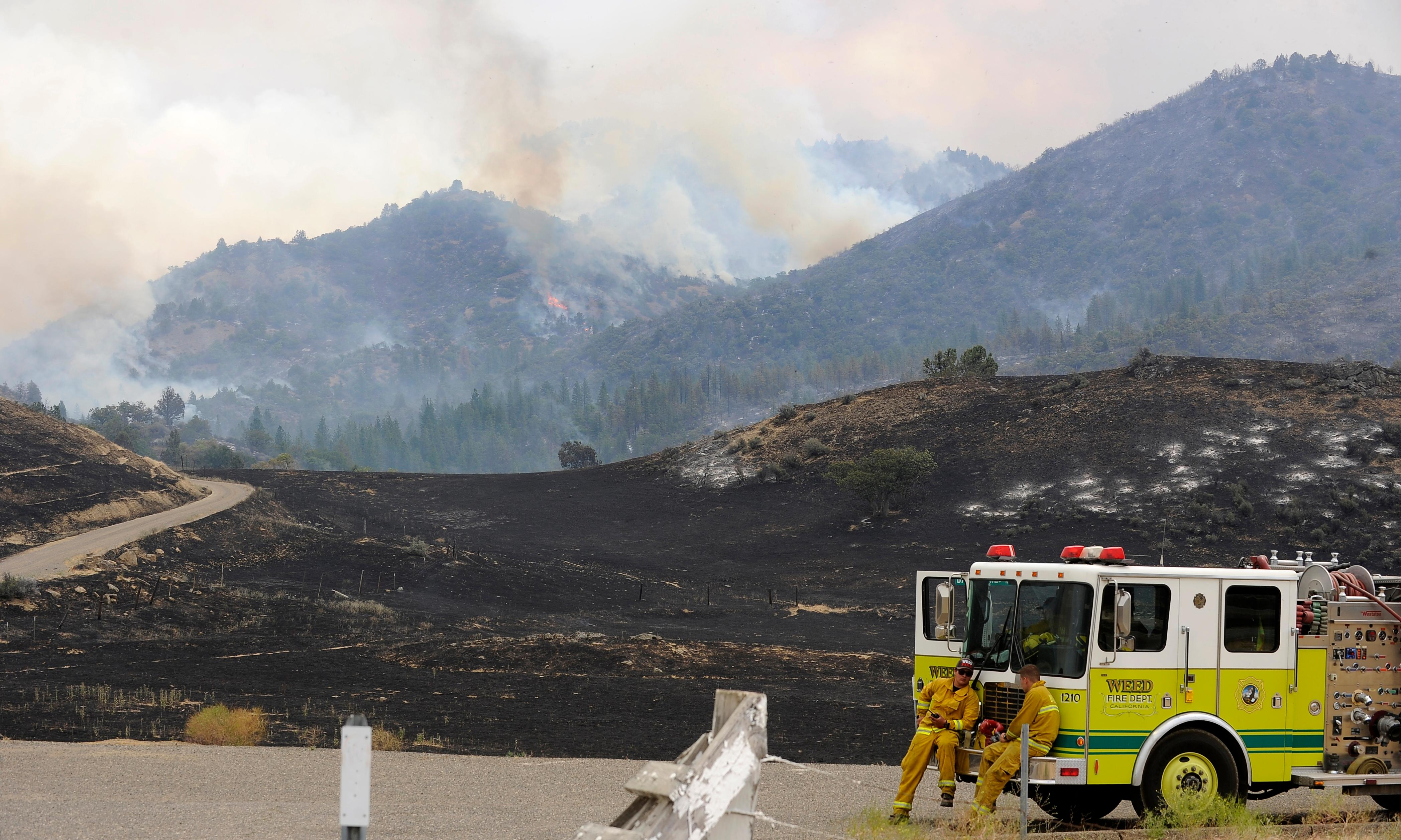 Andy Atkinson / Mail Tribune<br>Fire crews rest at the Baily Hill Road freeway interchange in Northern California as the hillside still blazes south of the Oregon-California border Friday afternoon.