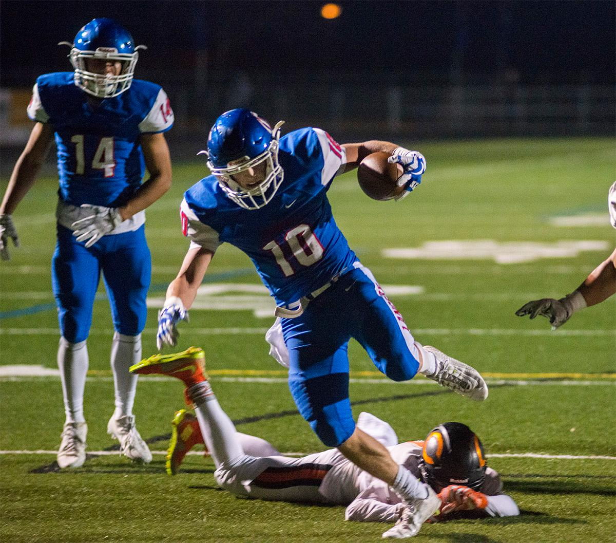 Churchill Lancers Tyson Bennion (#10) jumps over Crater Comets defense to gain more yards. Churchill defeated Crater 63-21 on Friday at their homecoming game. Churchill remains undefeated with a conference record of 9-0. Photo by Rhianna Gelhart, Oregon News Lab