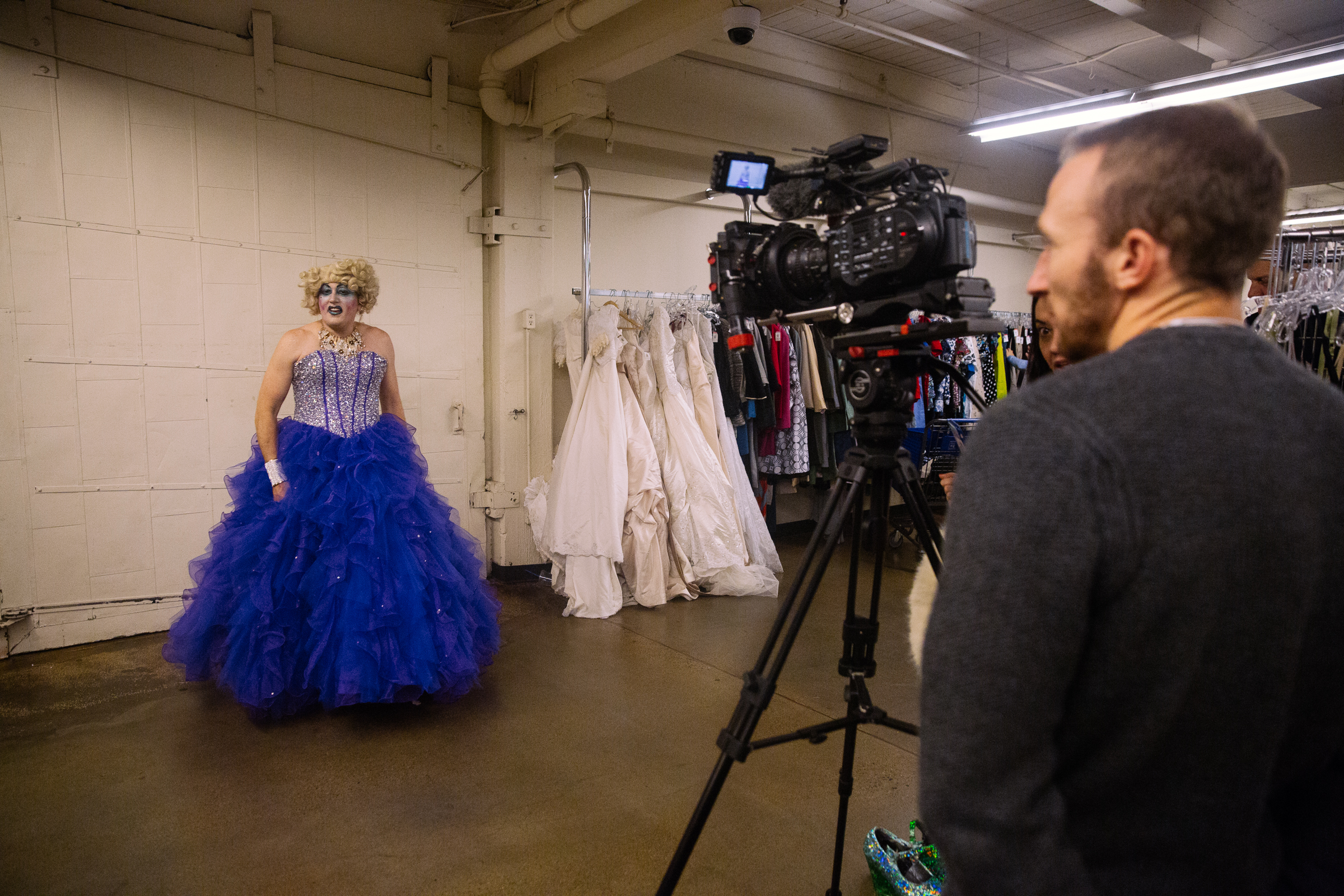 Drag Queen Miss Frida Layy tries on a dress for a Seattle Refined Story about the Seattle Goodwill Glitter Sale. (Photo courtesy of Seattle Goodwill)<p></p>