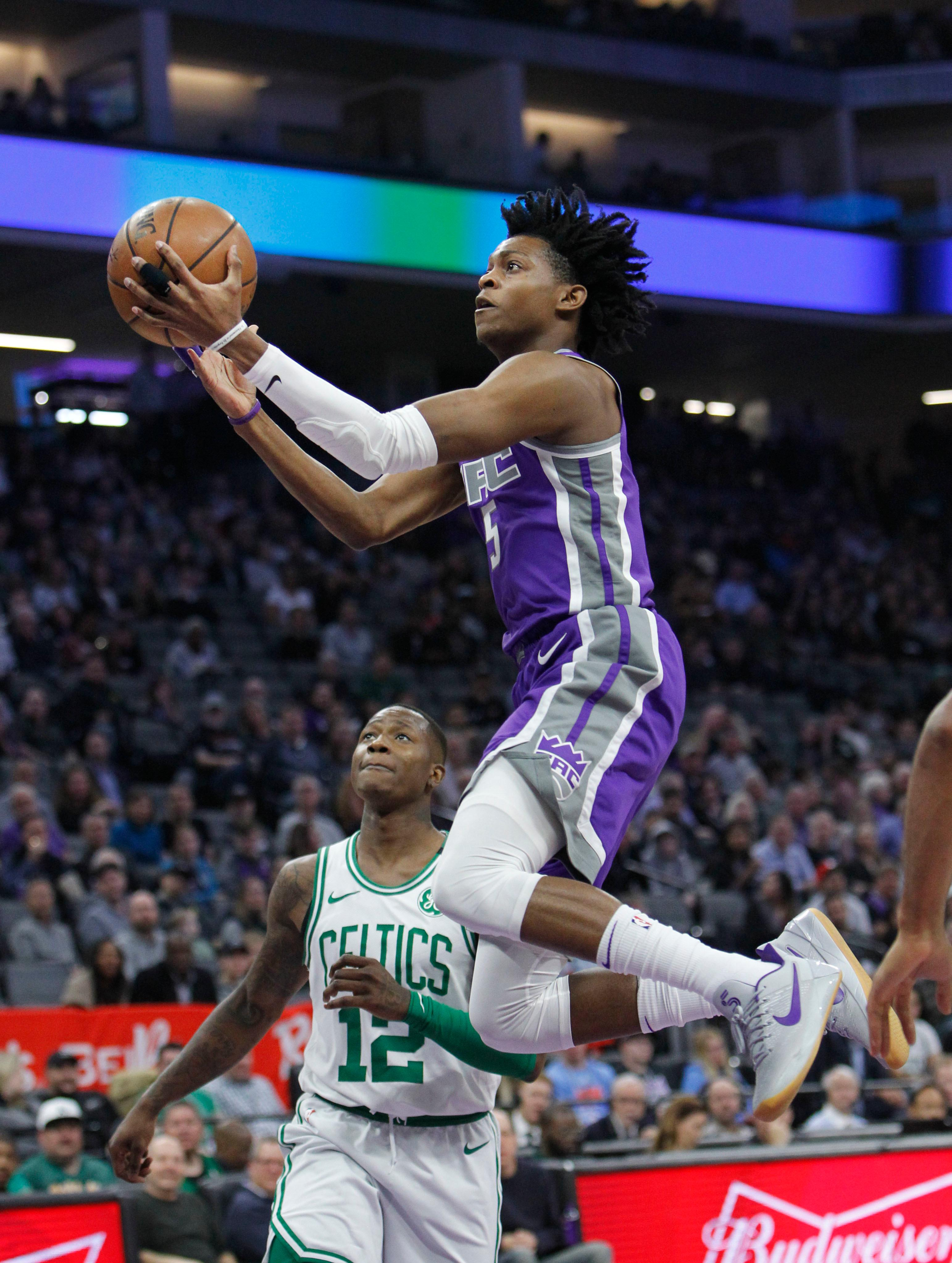 Sacramento Kings guard De'Aaron Fox (5) drives to the basket against Boston Celtics guard Terry Rozier (12) during the first half of an NBA basketball game in Sacramento, Calif., Sunday, March 25, 2018. (AP Photo/Steve Yeater)