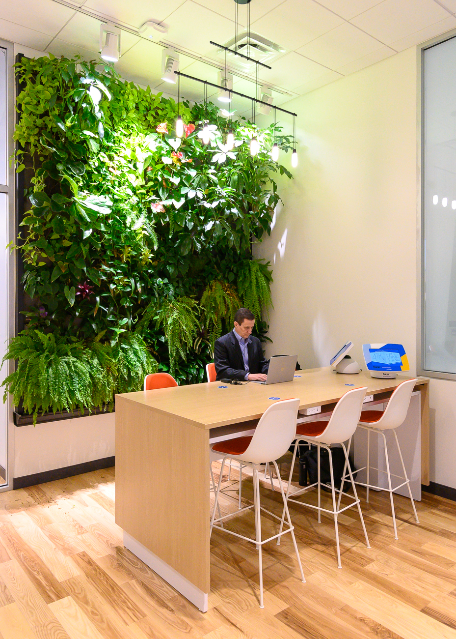 "In the back of the open room is a corner with a massive Urban Blooms living wall. The table is equipped with built-in, internet-capable computers as well as induction chargers; place your phone on the ""coaster"" and it will charge. / Image: Phil Armstrong, Cincinnati Refined // Published: 2.25.20"