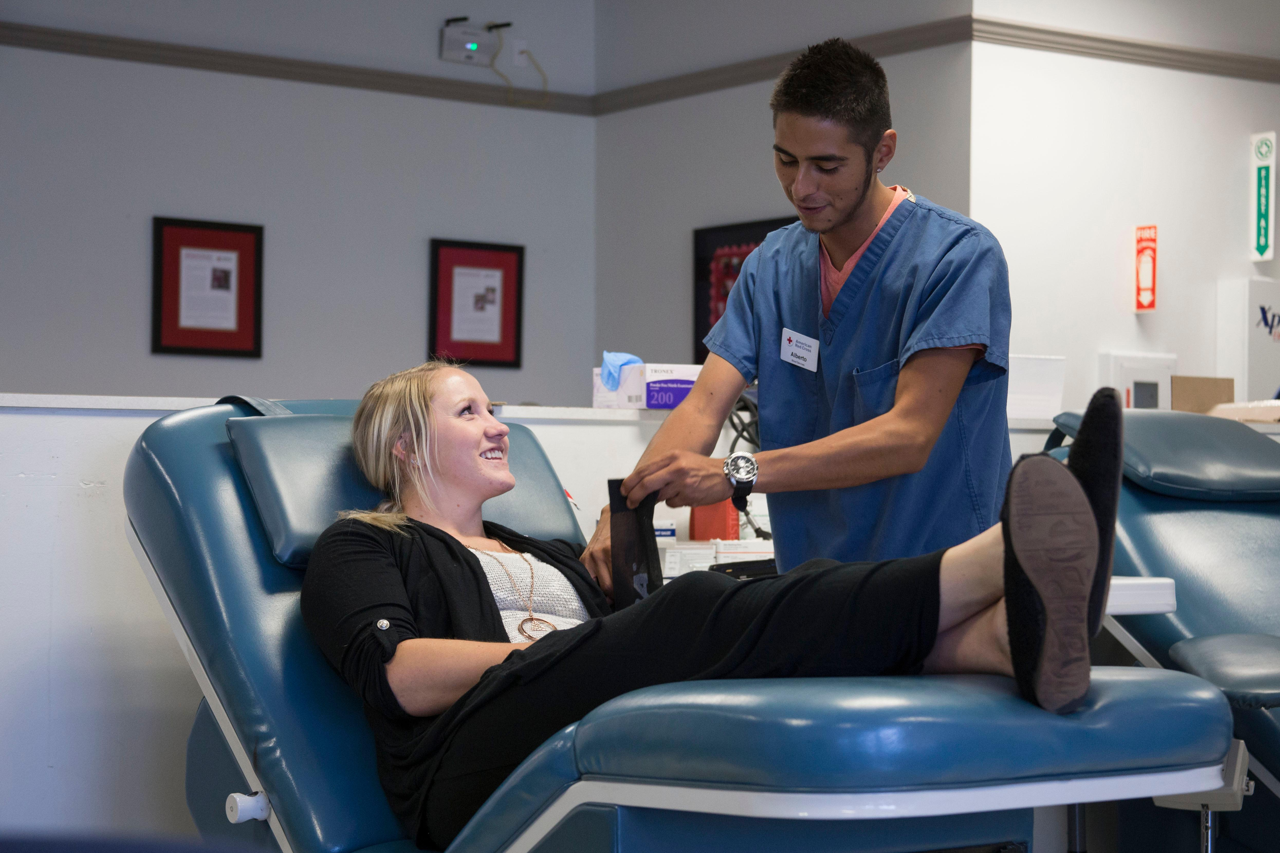 July 21, 2015. Salt Lake Donor Center, Salt Lake City, Utah. 23-year-old Kelsie Webster chats with Red Cross staffer Alberto Duenas while donating blood for the first time. Photo by Amanda Romney/American Red Cross