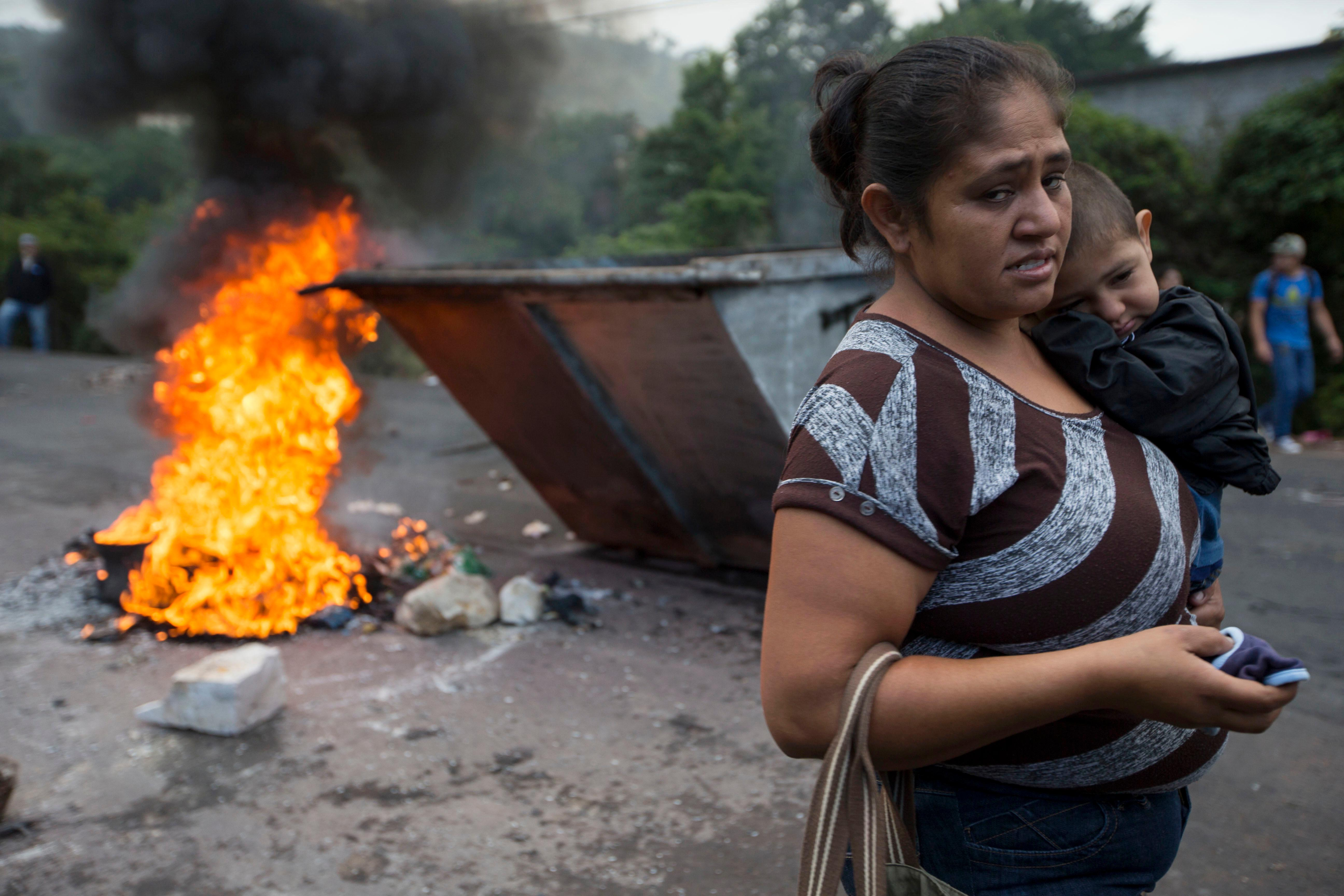 A woman, carrying a child, walks past a burning barricade erected by anti-government demonstrators blocking the road to Valle de los Angeles, on the outskirts of Tegucigalpa, Honduras, Thursday, Dec. 7, 2017. The government has lifted the curfew it imposed last week for nine of the country's 18 provinces, but left it in place for the two biggest cities, Tegucigalpa and San Pedro Sula, armed forces spokesman Jorge Cerrato said. (AP Photo/Moises Castillo)