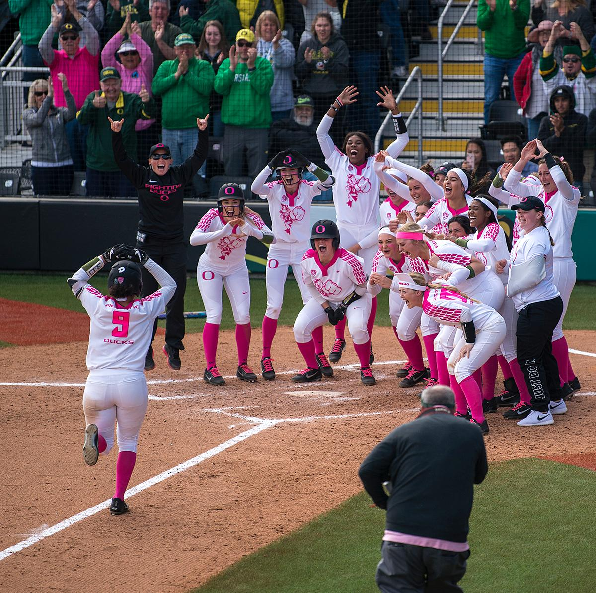 The Oregon Ducks team and assistant coach Chelsea Spencer cheer on outfielder Shannon Rhodes (#9) to home plate after her three-run walk-off homer in the final inning to win the game.The University of Oregon Ducks defeated the UCLA Bruins 3-0 in the final game of a three-game series Sunday afternoon at Jane Sanders Stadium. Shannon Rhodes hit a walk-off three-run homer in the bottom of the 7th inning to win the game. The Ducks improved to 25-5 overall and 2-1 in Pac-12 play. Photo by Abigail Winn, Oregon News Lab