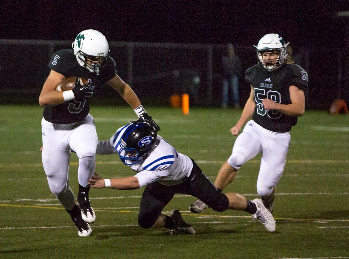 Sheldon's Patrick Herbert (#5) avoids a tackle by a South Medford Panther. South Medford Panther Chase Cota (#23) is brought down after attempting to break through Sheldon's defense. The South Medford Panthers defeated the Sheldon Irish 31 – 14 at Sheldon High School on Friday, October 20. Photo by Kit MacAvoy, Oregon News Lab