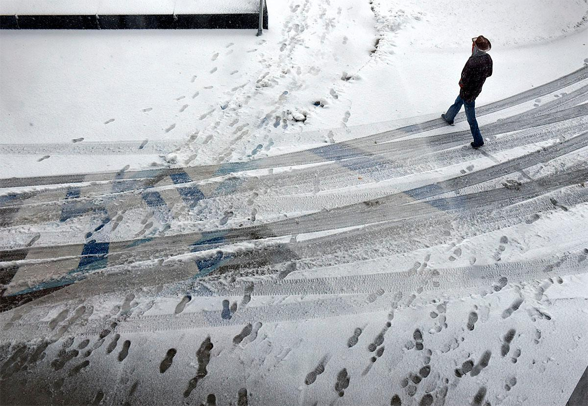A man walks in the snow near the entrance to the St. Cloud Public Library Friday, Nov. 18, 2016 in St. Cloud, Minn. Forecasters predict blizzard conditions beginning Friday across central Minnesota where 6 to 12 inches of snow could accumulate by nightfall. Winds of 50 to 60 mph are expected to make travel very difficult.(Dave Schwarz/St. Cloud Times via AP)