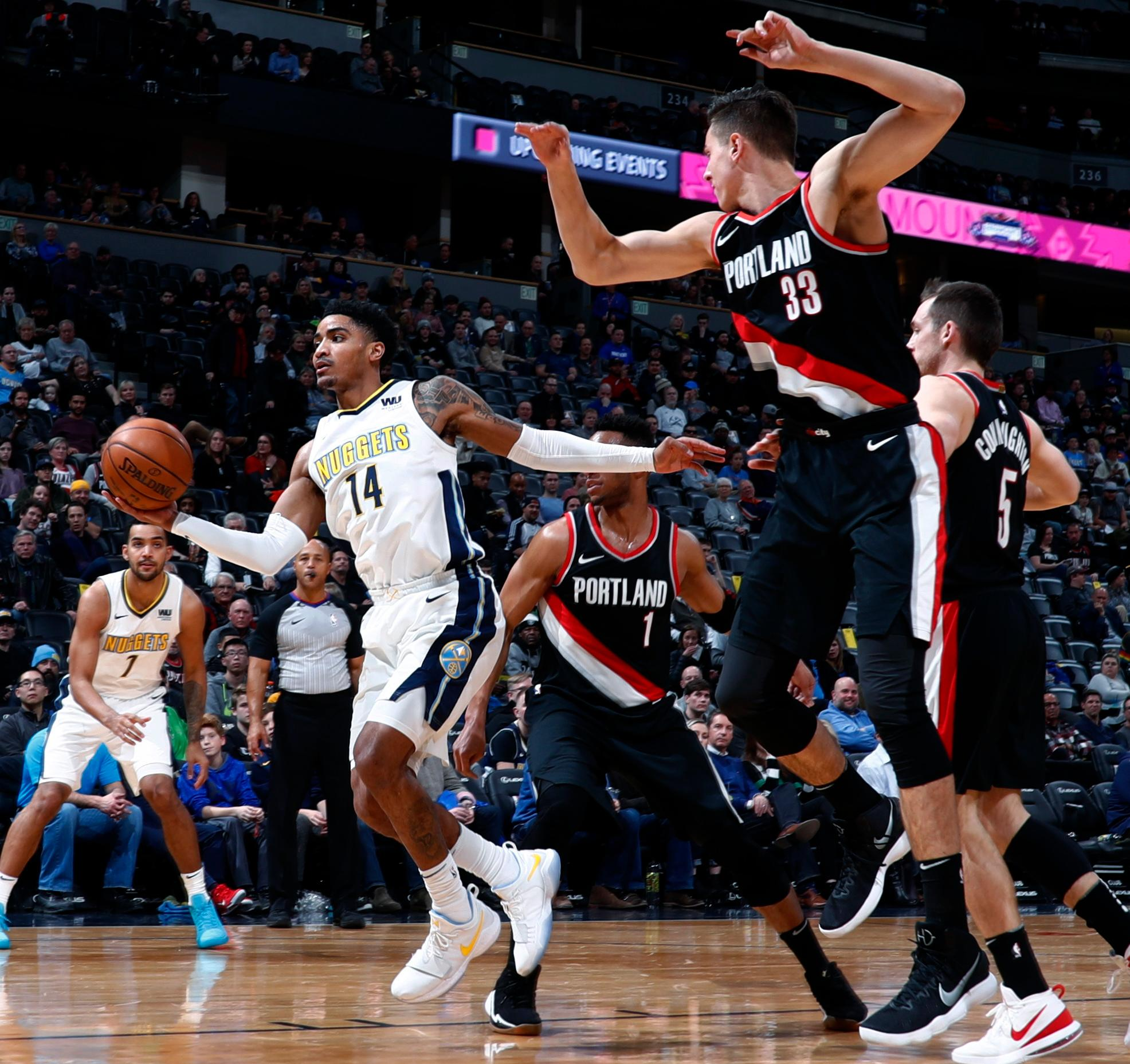 Denver Nuggets guard Gary Harris pulls in the ball as Portland Trail Blazers center Zach Collins (33) defends in the first half of an NBA basketball game Monday, Jan. 22, 2018, in Denver. (AP Photo/David Zalubowski)