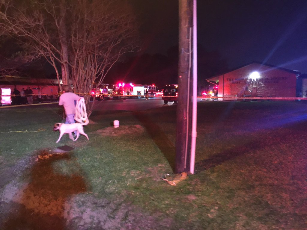 A person walking a dog away from the scene of a fire in Beaumont, where dozens of animals were killed according to fire officials. (Photo by Tiffany Murphy KFDM)