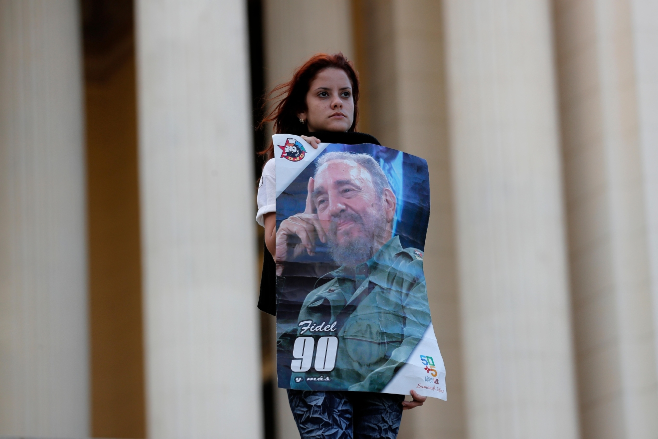 A student stands at attention holding images of Fidel Castro at the university where Castro studied law as a young man, during a vigil in Havana, Cuba, Sunday, Nov. 27, 2016. (AP Photo/ Dario Lopez-Mills)