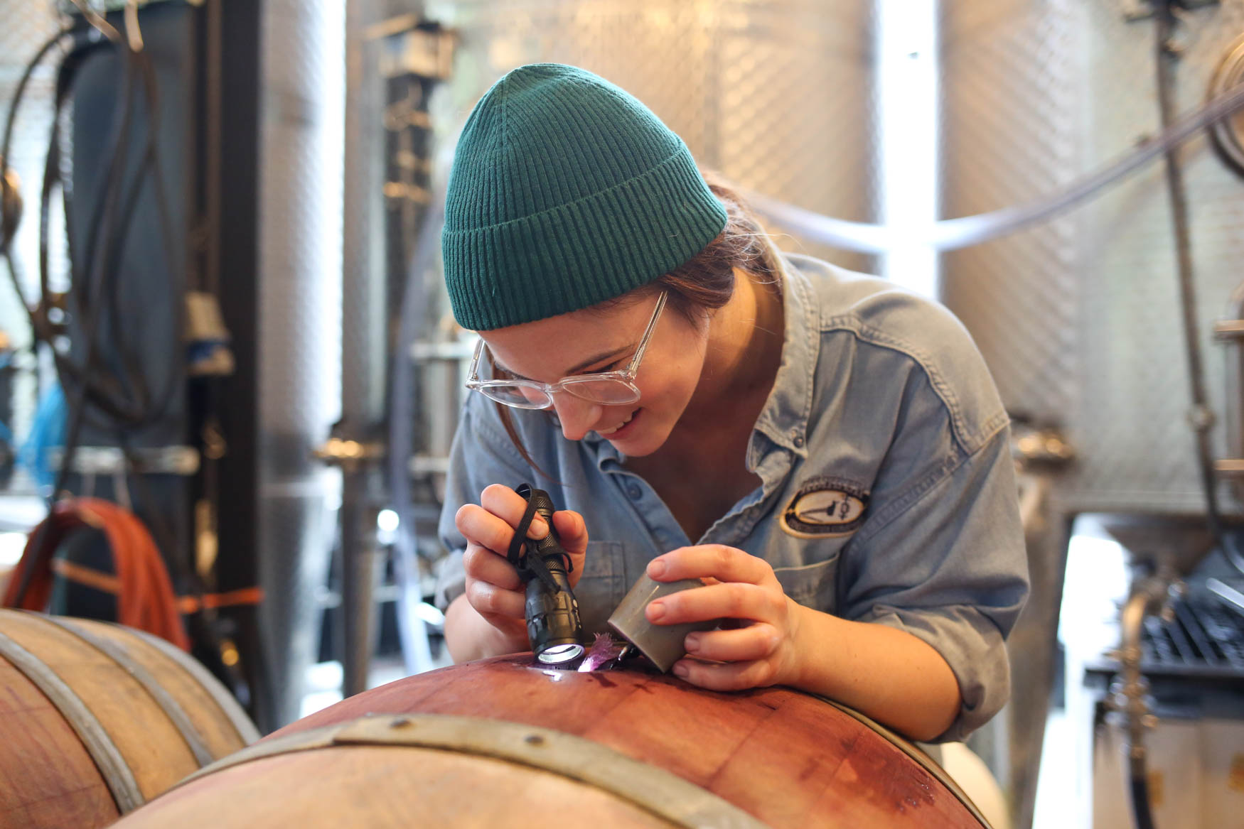 Cellar worker{ }Claire Corbin inspects the wine. (Amanda Andrade-Rhoades/DC Refined)