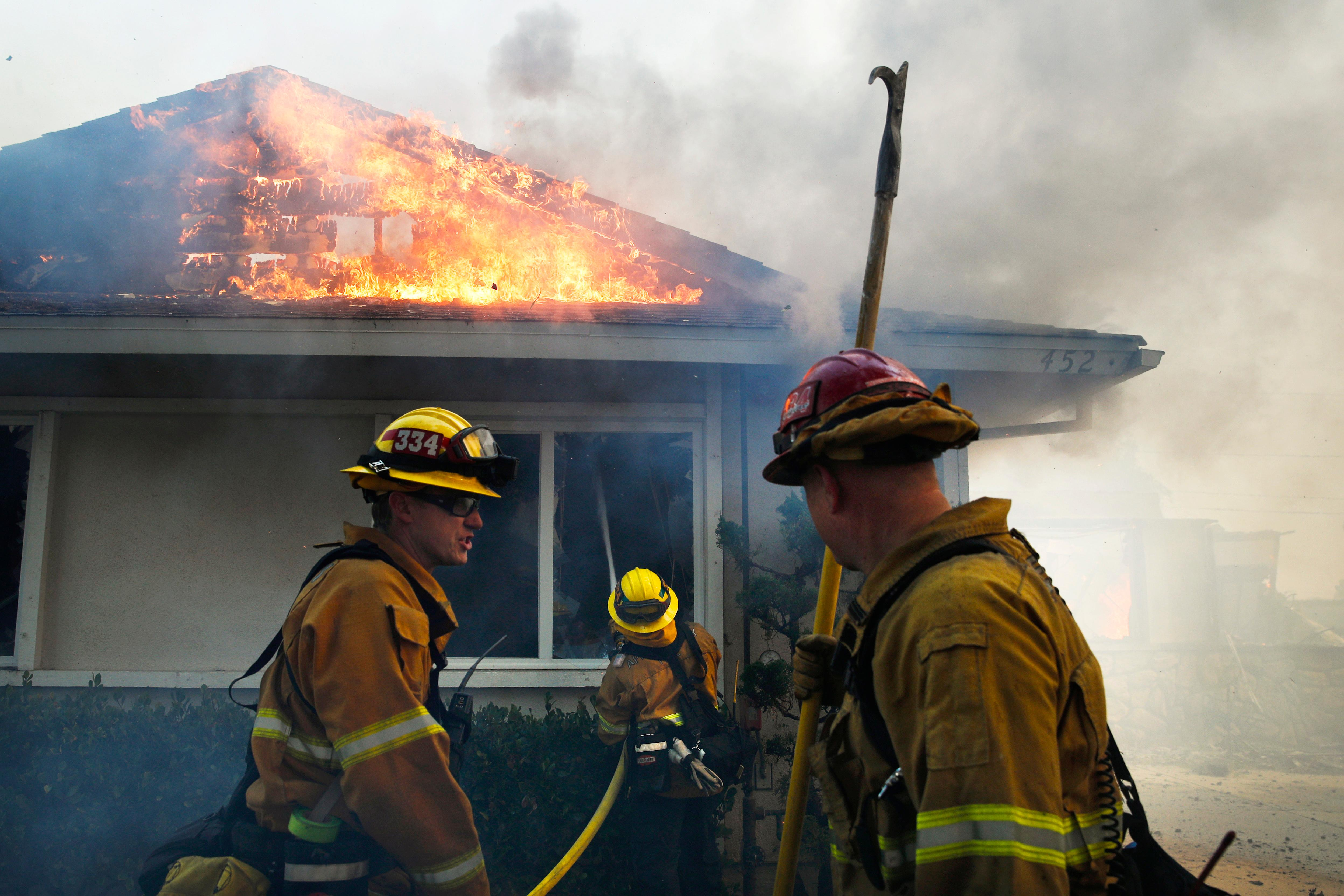 Firefighters put out a fire burning a home Tuesday, Dec. 5, 2017, in Ventura, Calif. Raked by ferocious Santa Ana winds, explosive wildfires northwest of Los Angeles and in the city's foothills burned a psychiatric hospital and scores of homes Tuesday and forced the evacuation of tens of thousands of people. (AP Photo/Jae C. Hong)