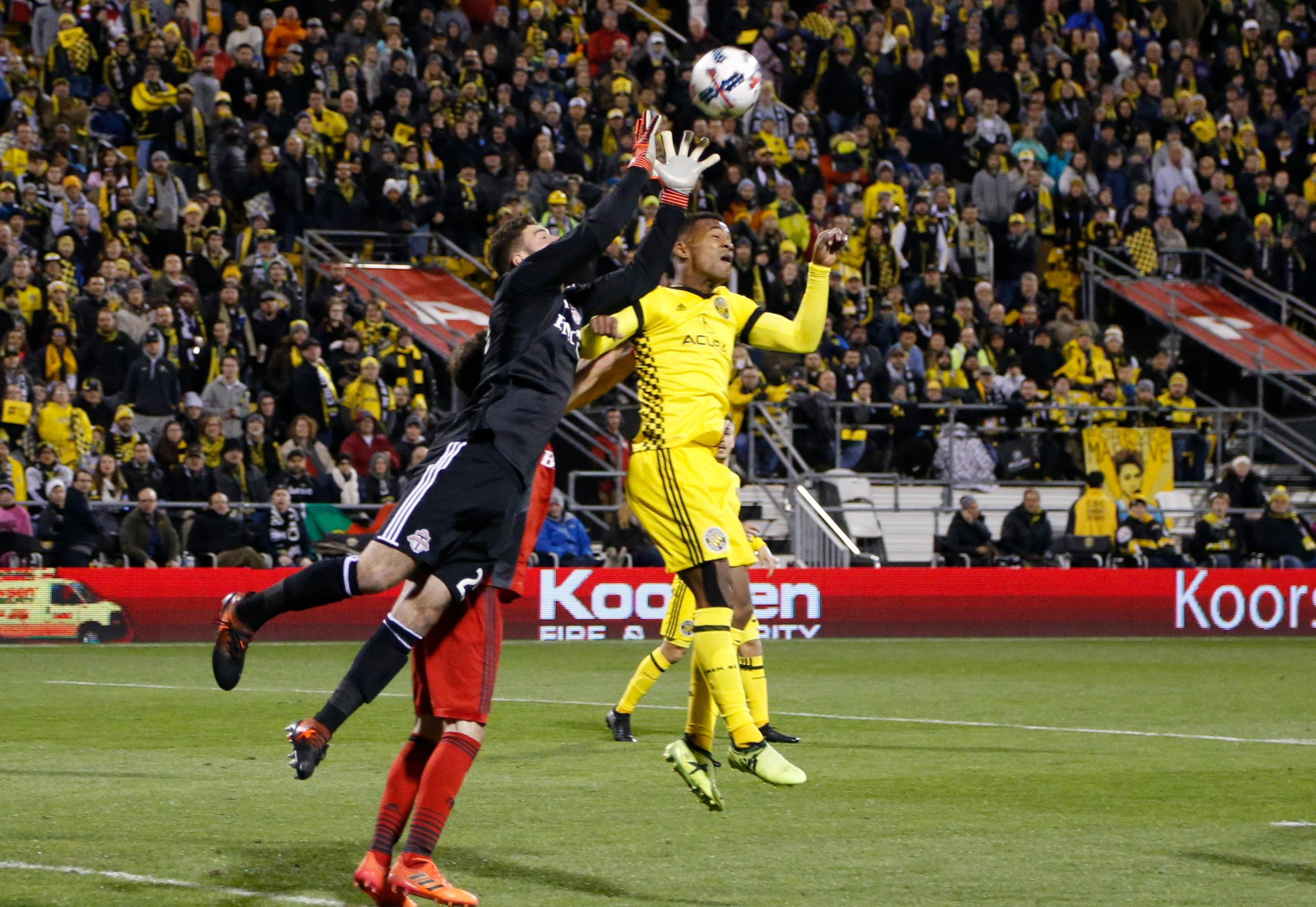 Toronto FC's Alex Bono, left, makes a save over Columbus Crew's Ola Kamara during the first half of an MLS Eastern Conference championship soccer match Tuesday, Nov. 21, 2017, in Columbus, Ohio. (AP Photo/Jay LaPrete)
