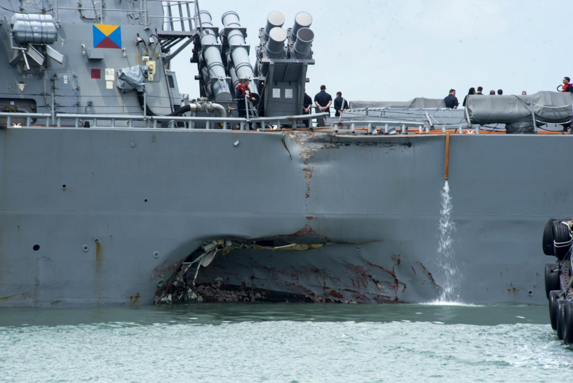 "Damage to the portside is visible as the Guided-missile destroyer USS John S. McCain (DDG 56) steers towards Changi naval base in Singapore following a collision with the merchant vessel Alnic MC Monday, Aug. 21, 2017. The USS John S. McCain was docked at Singapore's naval base with ""significant damage"" to its hull after an early morning collision with the Alnic MC as vessels from several nations searched Monday for missing U.S. sailors. (Mass Communication Specialist 2nd Class Joshua Fulton/U.S. Navy photo via AP)"