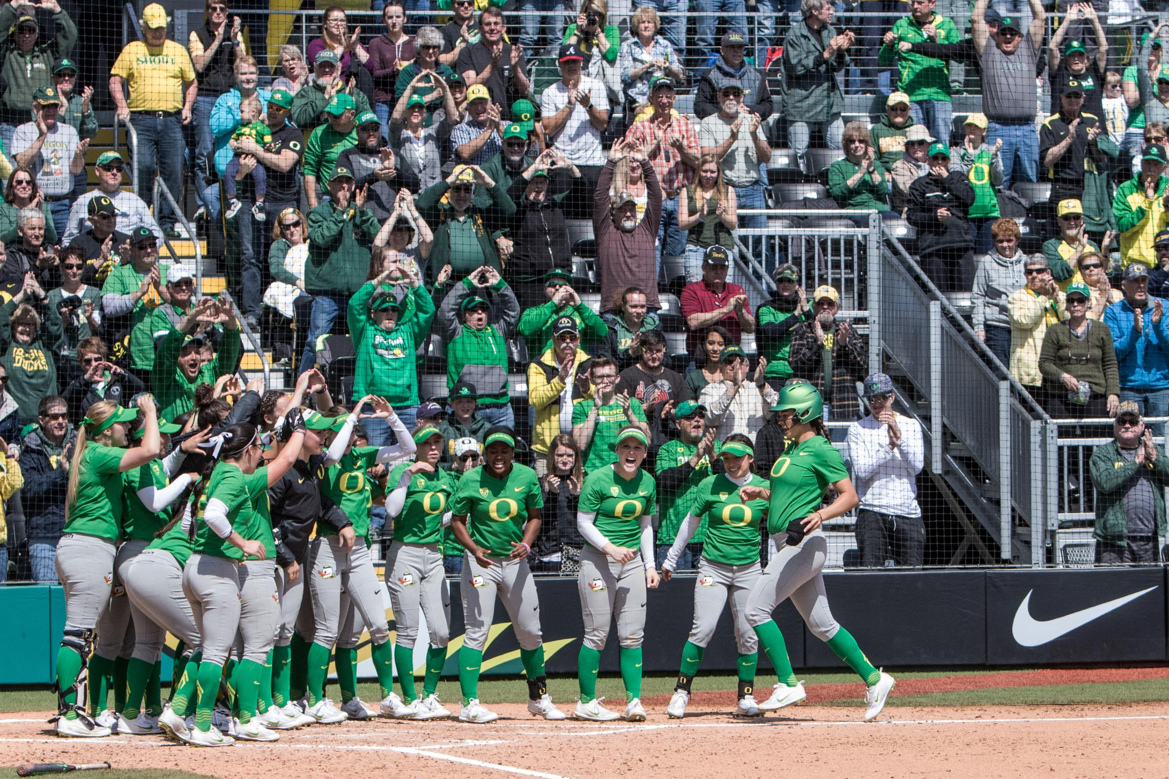 The Oregon Ducks celebrate teammate Niiki Udria (#3) as she finishes rounding the bases following a two-run homerun. In the final game of a three-game series, the University of Washington Huskies defeated the Oregon Ducks 5-3.  The Ducks led through the bottom of the 7th inning, but Washington's Morganne Flores (#47) tied it up with a two-run double.  Flores drove in two more runs in the 9th to take the lead.  Photo by Austin Hicks, Oregon News Lab