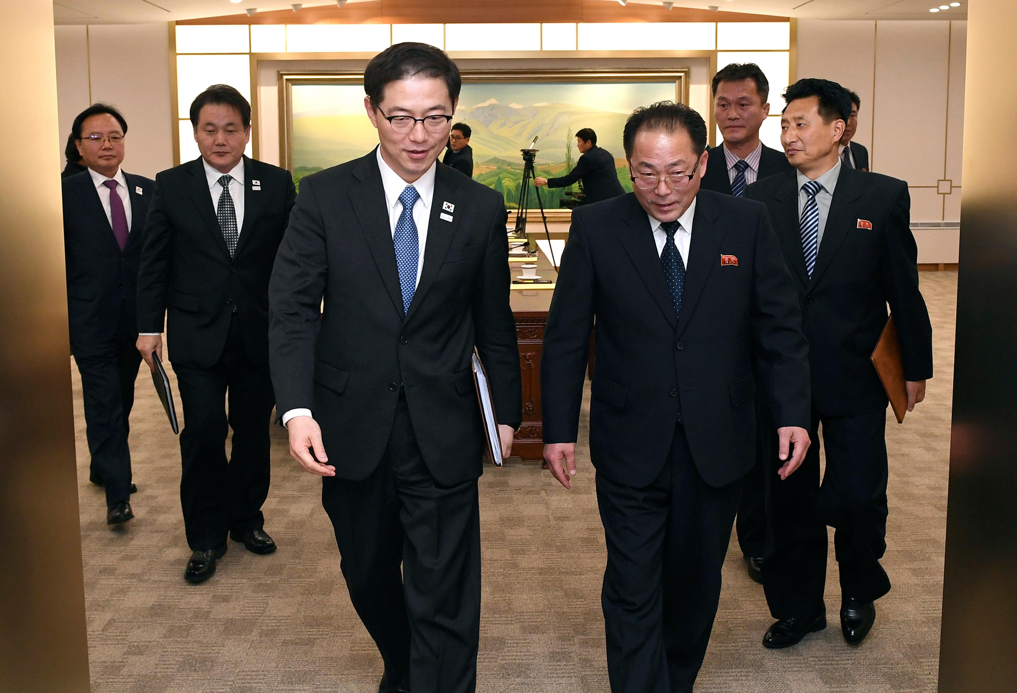 In this photo provided by South Korea Unification Ministry, South Korean Vice Unification Minister Chun Hae-sung, center left, and the head of North Korean delegation Jon Jong Su leave after a meeting at Panmunjom in the Demilitarized Zone in Paju, South Korea, Wednesday, Jan. 17, 2018. The rival Koreas agreed Wednesday to form their first unified Olympic team and have their athletes parade together during the opening ceremony of next month's Winter Olympics in the South, Seoul officials said. (South Korea Unification Ministry via AP)