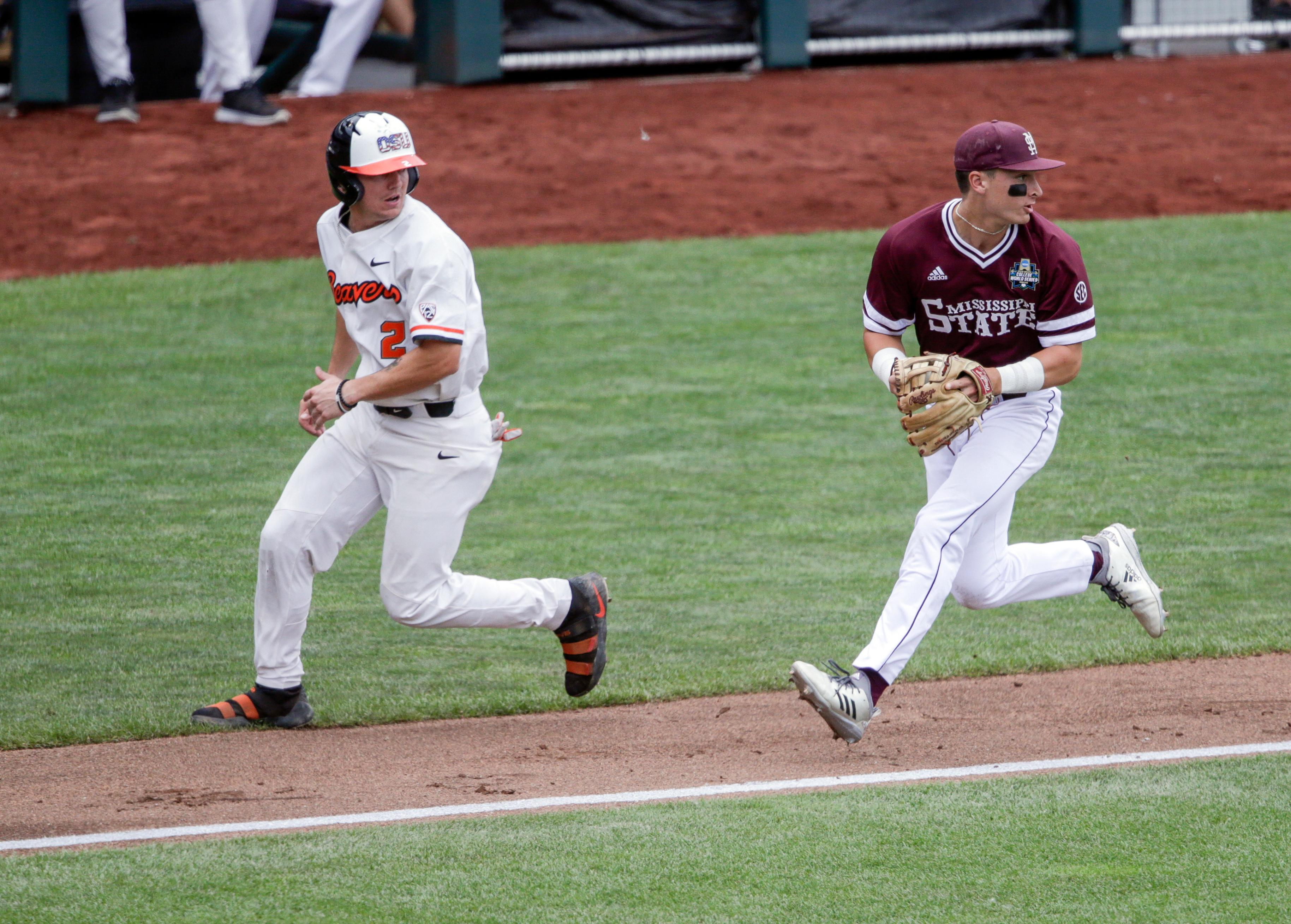 Mississippi State third baseman Justin Foscue, looks toward second base after tagging out Oregon State's Cadyn Grenier (2) in a rundown between third base and home in the first inning of an NCAA College World Series baseball game in Omaha, Neb., Friday, June 22, 2018. (AP Photo/Nati Harnik) right,