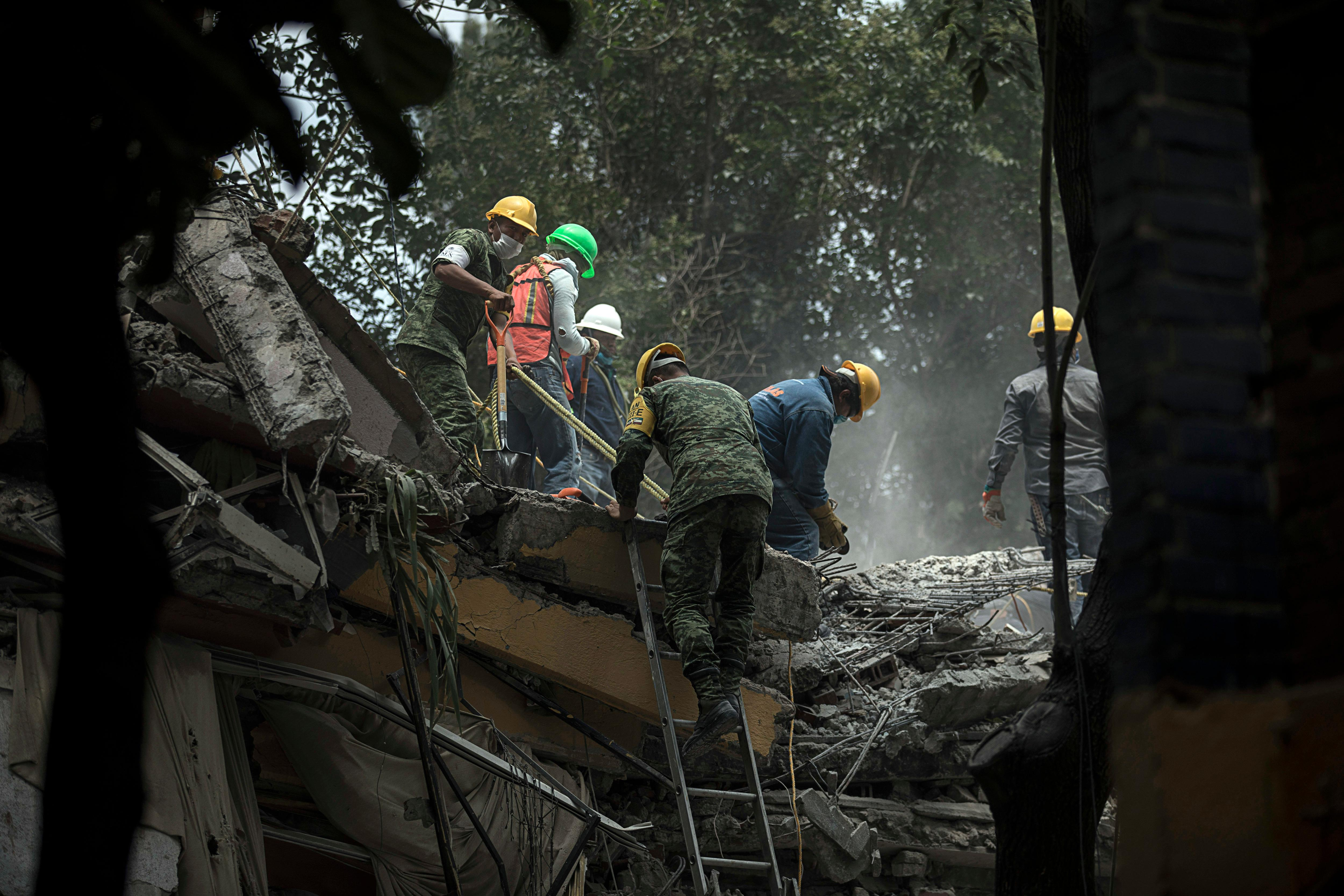Rescue workers and volunteers search for survivors at the Unidad Habitacional Tlalpan 1-C in Mexico City, Wednesday Sept. 20, 2017. A magnitude 7.1 earthquake has stunned central Mexico, killing more than 100 people as buildings collapsed in plumes of dust. (AP Photo/Miguel Tovar)