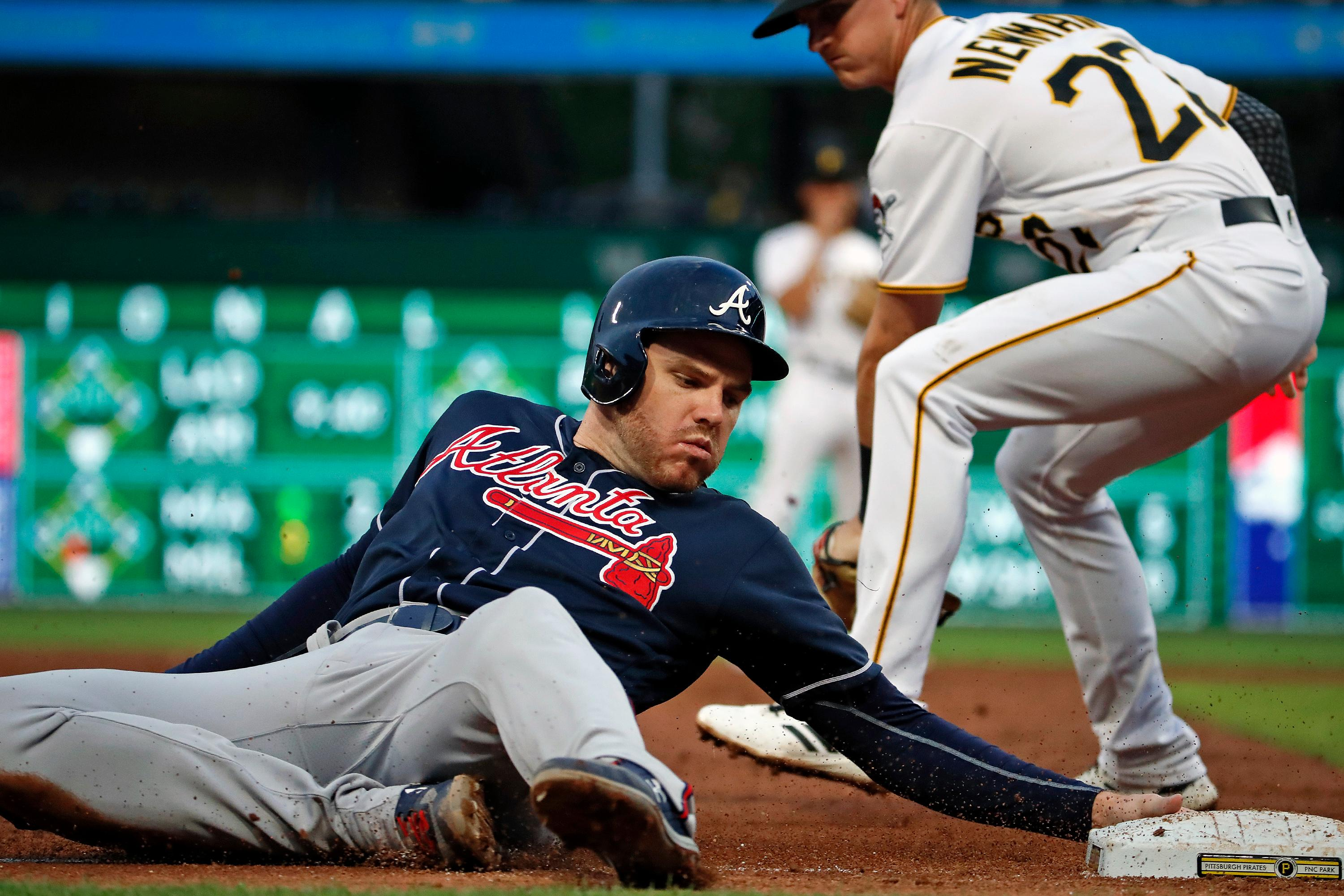 Atlanta Braves' Freddie Freeman, left, advances to third ahead of the attempted tag by Pittsburgh Pirates third baseman Kevin Newman on a pop foul by Austin Riley during the third inning of a baseball game in Pittsburgh, Tuesday, June 4, 2019.(AP Photo/Gene J. Puskar)