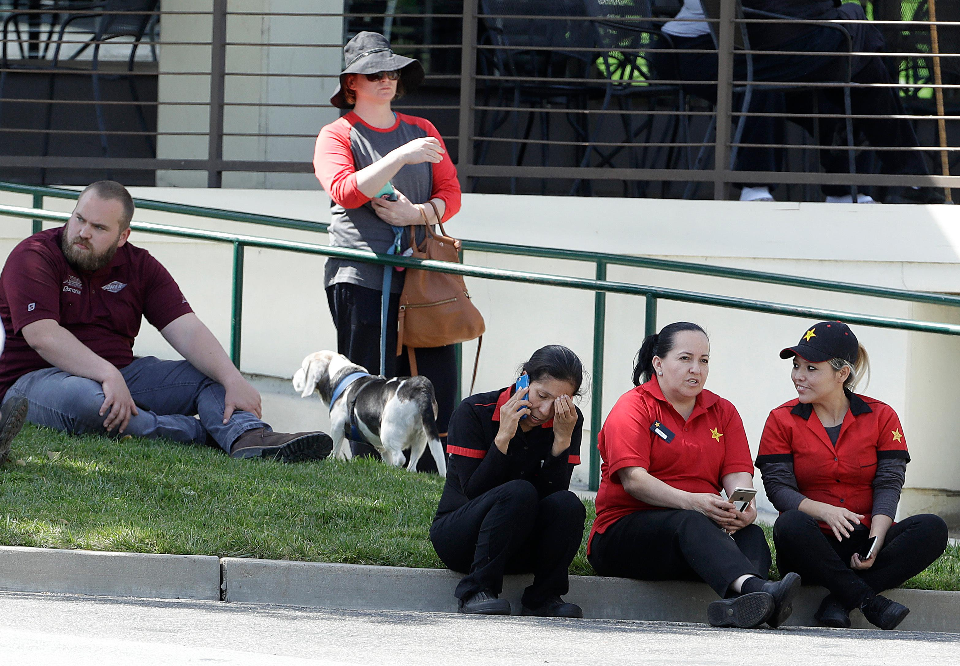 Carl's Jr. workers and others sit in a shopping center parking lot near YouTube's offices in San Bruno, Calif., Tuesday, April 3, 2018. A woman opened fire at YouTube headquarters Tuesday, setting off a panic among employees and wounding several people before fatally shooting herself, police and witnesses said. (AP Photo/Jeff Chiu)