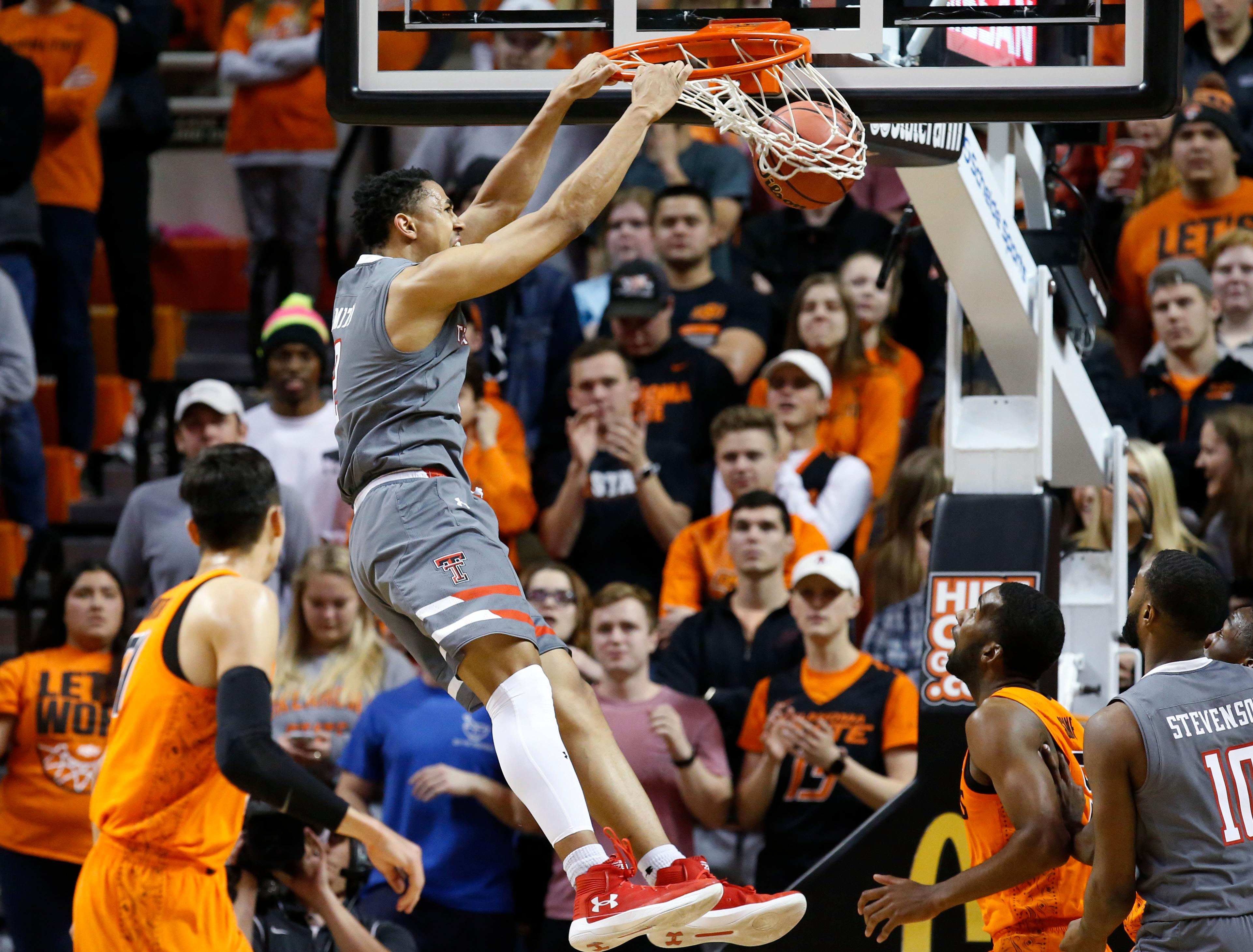 Texas Tech guard Zhaire Smith dunks between Oklahoma State guard Lindy Waters III, left, and guard Tavarius Shine, second from right, during the first half of an NCAA college basketball game in Stillwater, Okla., Wednesday, Feb. 21, 2018. (AP Photo/Sue Ogrocki)