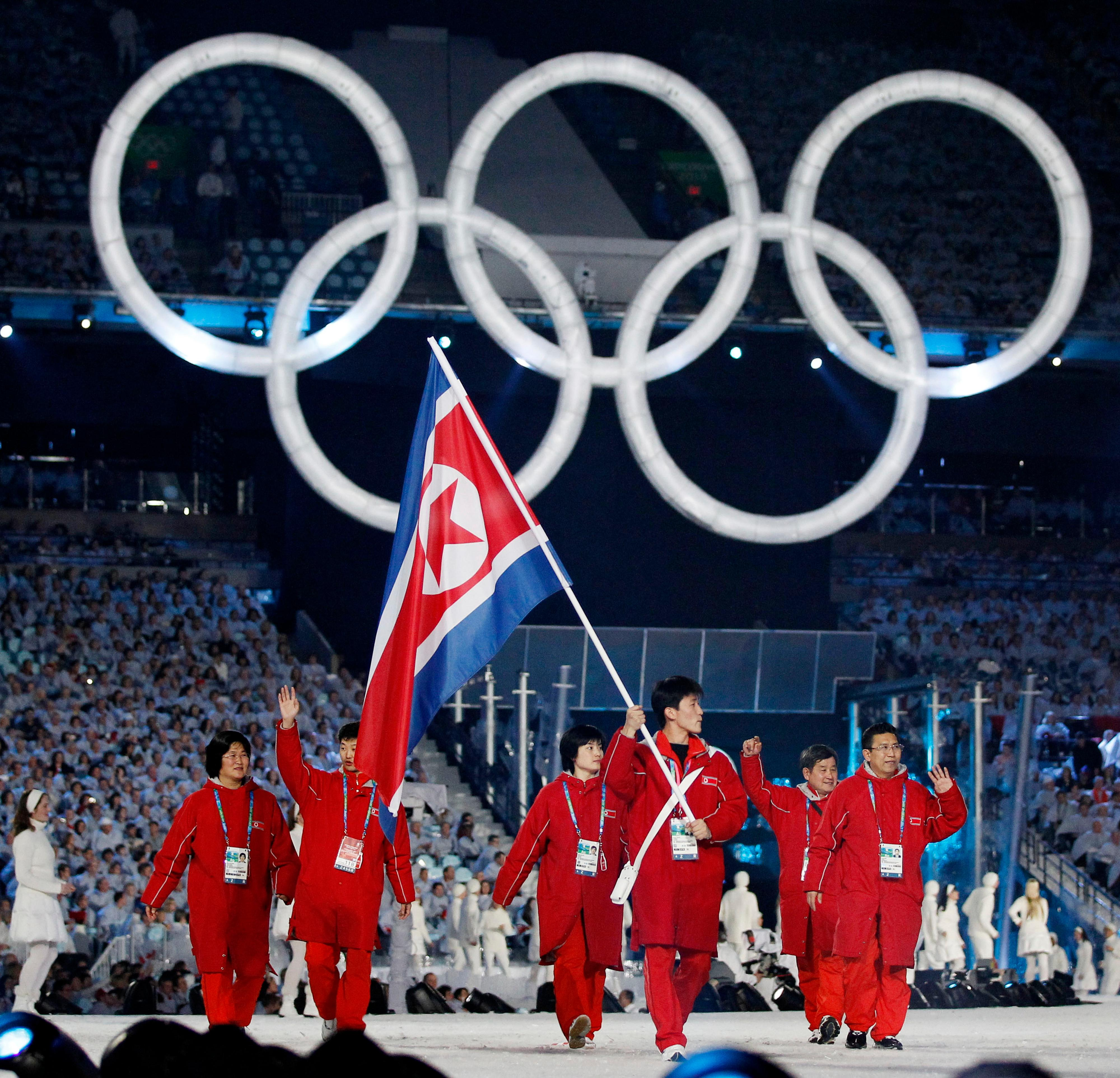 FILE - In this Feb 12, 2010 file photo, North Korea's Song Chol Ri carries the flag during the opening ceremony for the Vancouver 2010 Olympics in Vancouver, Canada. Seven months ahead of the Pyeongchang Olympics, many in South Korea, including new liberal President Moon Jae-in, hope to use the Games as a venue to promote peace with rival North Korea. To do so, the North's participation is essential, but an ongoing nuclear tension and a lack of winter sports athletes in North Korea could ruin the attempts at reconciliation. (AP Photo/Mark Baker, File)