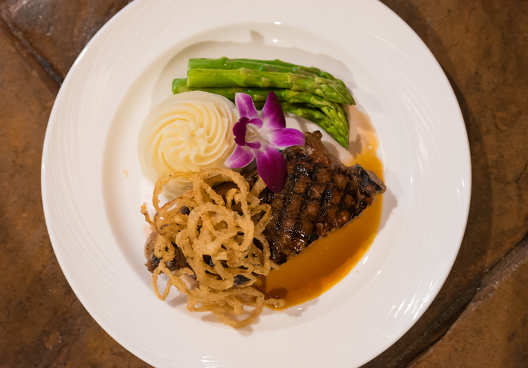 14 oz. dry-aged New York strip steak topped with fried onion straws and veal demi-glaze with garlic mashed potatoes and steamed asparagus / Image: Sherry Lachelle Photography // Published: 3.21.18