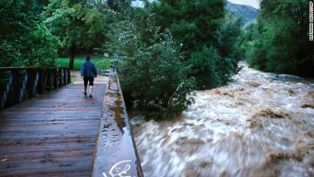 During a break in the rain, a woman walks over a footbridge past the raging Boulder Creek in Boulder on September 13.