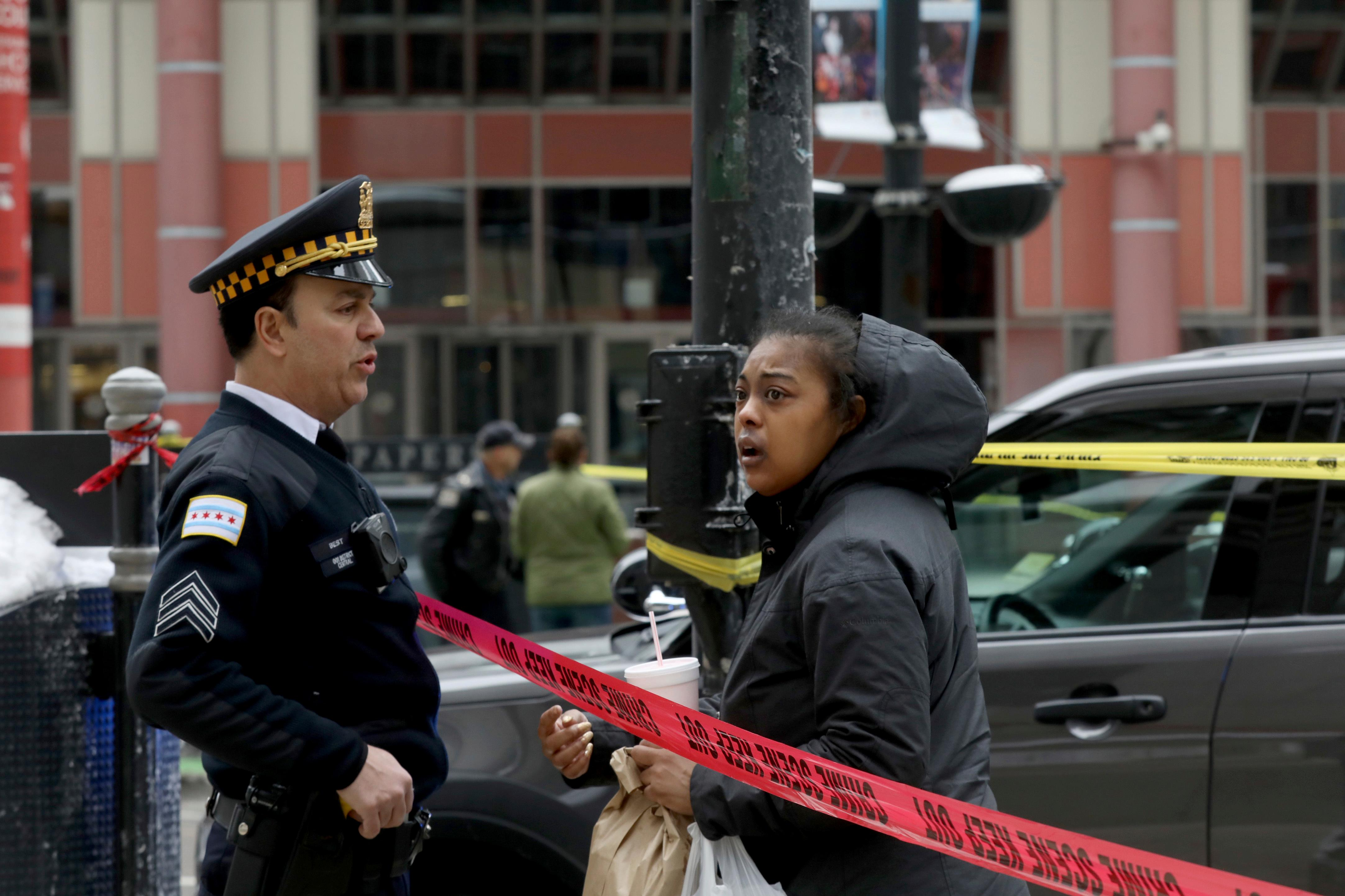 A Chicago Police officer speaks a with a pedestrian at the scene where an off-duty officer was shot while assisting a tactical team at a state government office building, Tuesday, Feb. 13, 2018, in Chicago. (John J. Kim/Chicago Tribune via AP)