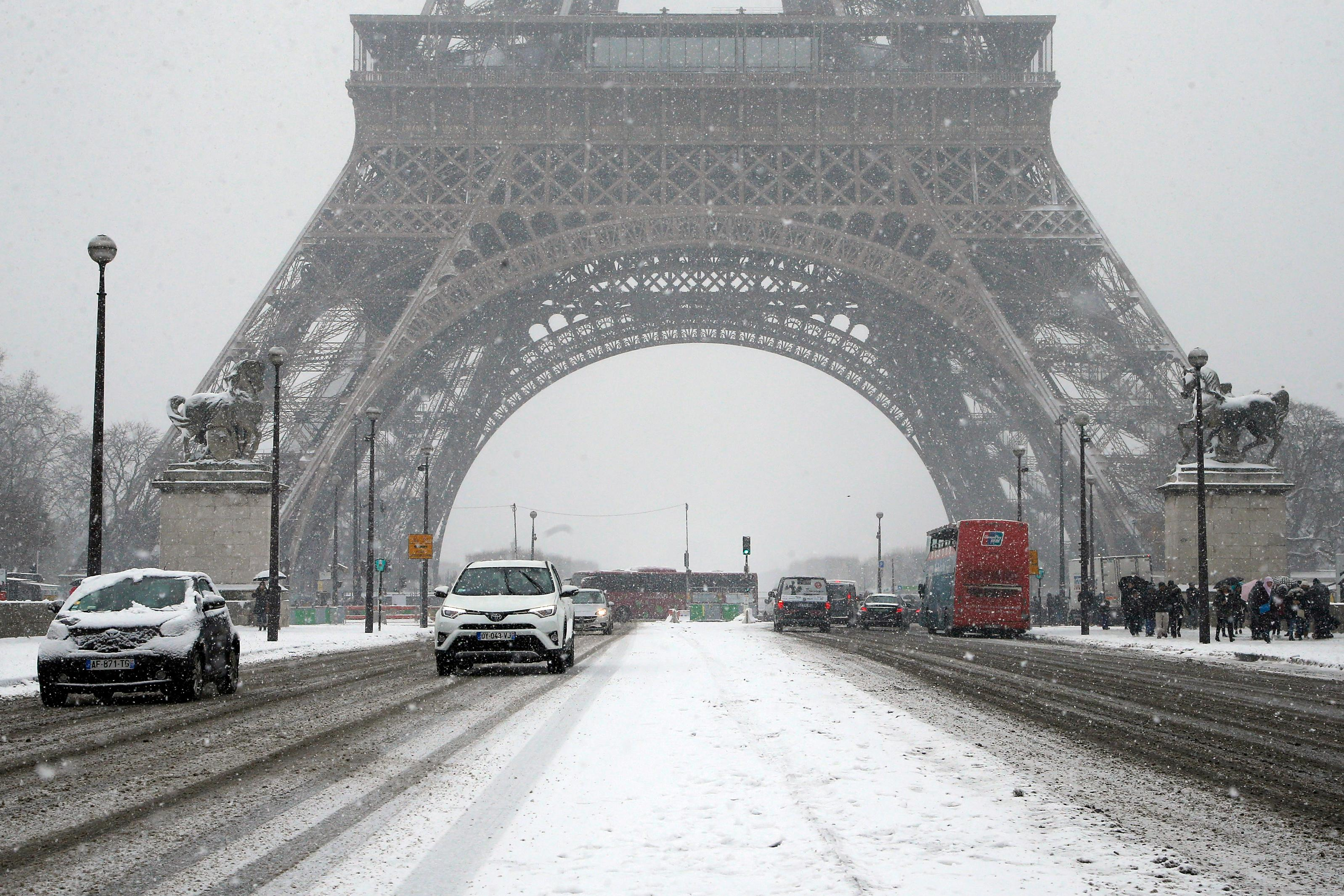 Cars drive over Iena bridge during a snowfall in Paris, France, Friday, Feb. 9, 2018. The Eiffel Tower is closed and authorities are telling drivers in the Paris region to stay home as snow and freezing rain have hit a swath of France ill-prepared for the wintry weather. (AP Photo/Michel Euler)