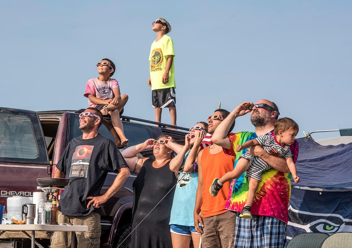 "Mylo, Paul, Julian, Wynter, Cori, Paul Sr., and Sam combine their family names to make the ""Bremiti Campers"" in honor of the eclipse. They stand in the campsite looking up with their solar filter glasses on to see the eclipse in motion. Photo by Cheyenne Thorpe, Oregon News Lab"