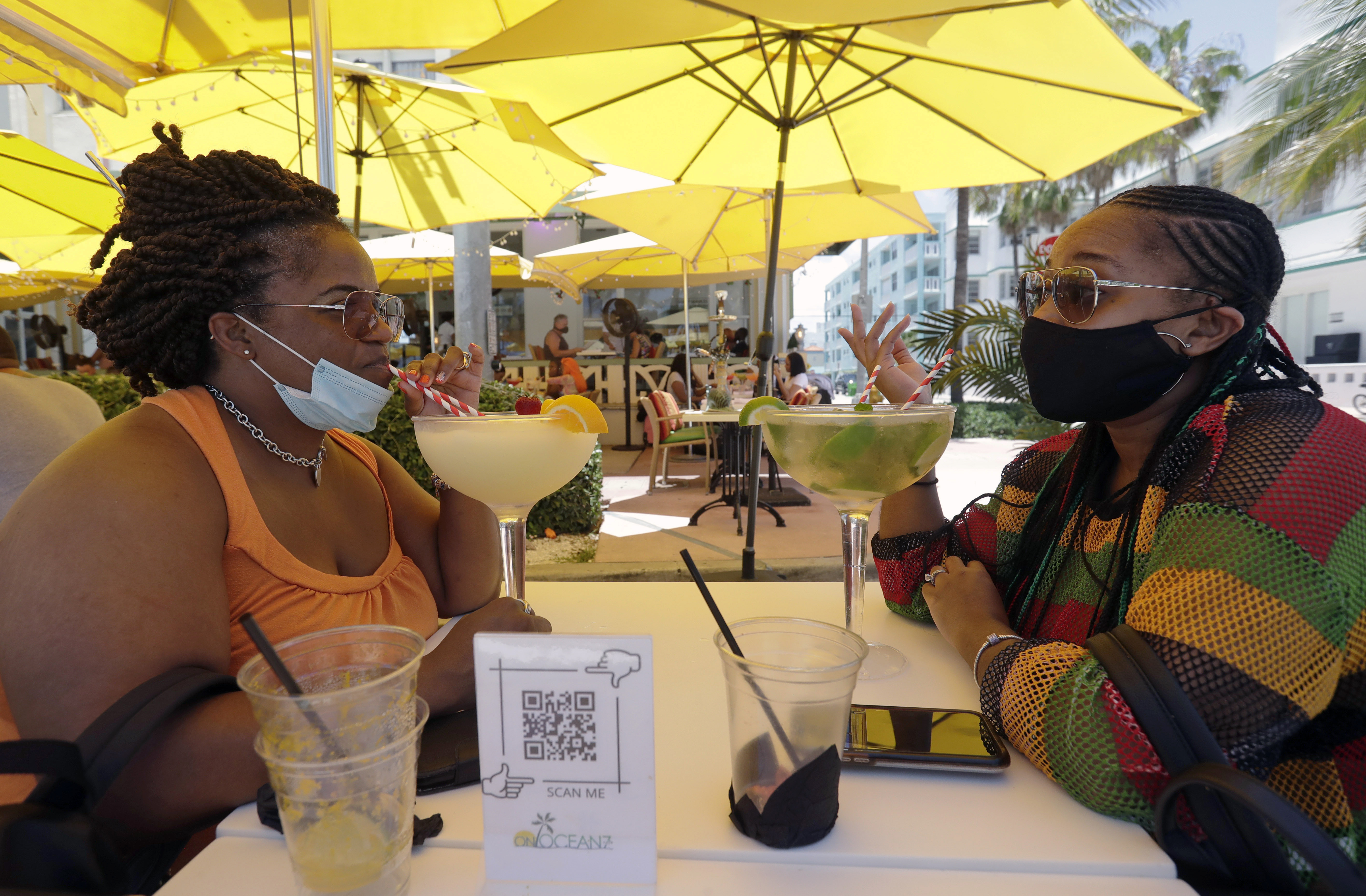 Anita Anderson, left, of Grand Rapids, Mich., and her niece Tawnya Heggins of Houston, chat as they dine outside a restaurant on Miami Beach, Florida's famed South Beach, Friday, June 26, 2020. Florida banned alcohol consumption at its bars Friday as its daily confirmed coronavirus cases neared 9,000, a new record that is almost double the previous mark set just two days ago. (AP Photo/Wilfredo Lee)