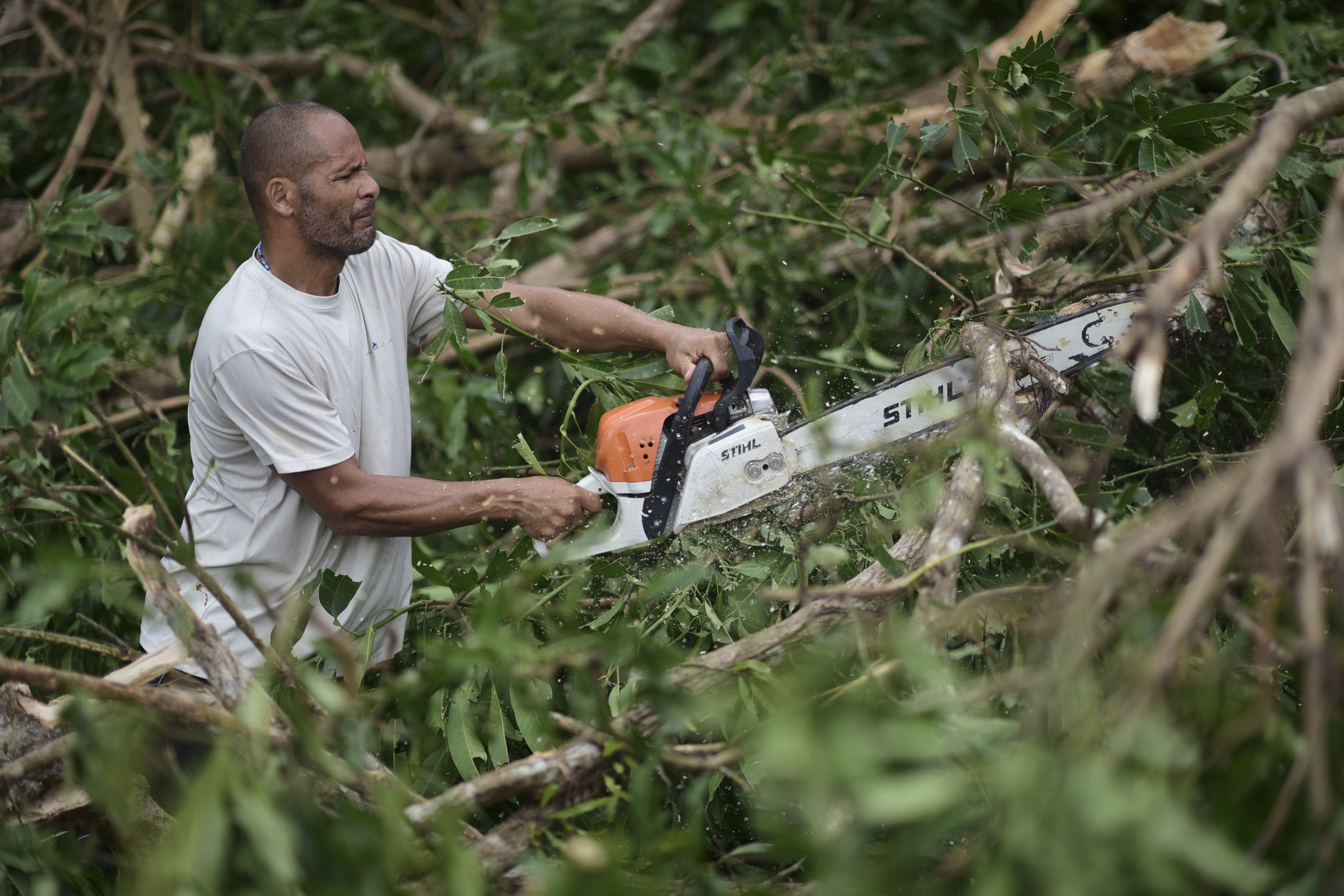 A municipal government worker clears a road after the passing of Hurricane Maria, in Yabucoa, Puerto Rico, Thursday, September 21, 2017. As of Thursday evening, Maria was moving off the northern coast of the Dominican Republic with winds of 120 mph (195 kph). The storm was expected to approach the Turks and Caicos Islands and the Bahamas late Thursday and early Friday. (AP Photo/Carlos Giusti)