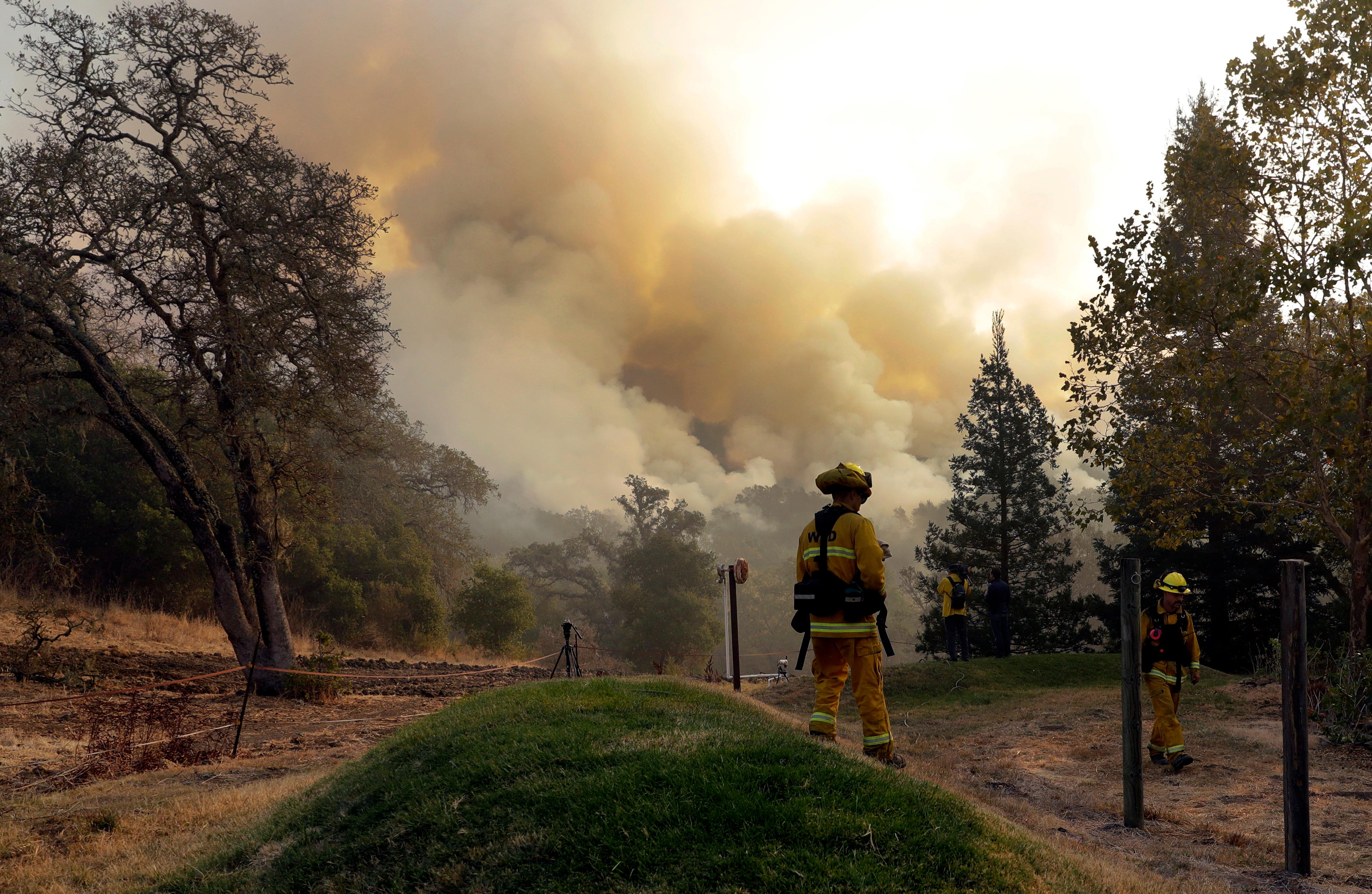 Firefighters walk along a containment line as a wildfire burns Saturday, Oct. 14, 2017, in Sonoma, Calif. (AP Photo/Marcio Jose Sanchez)