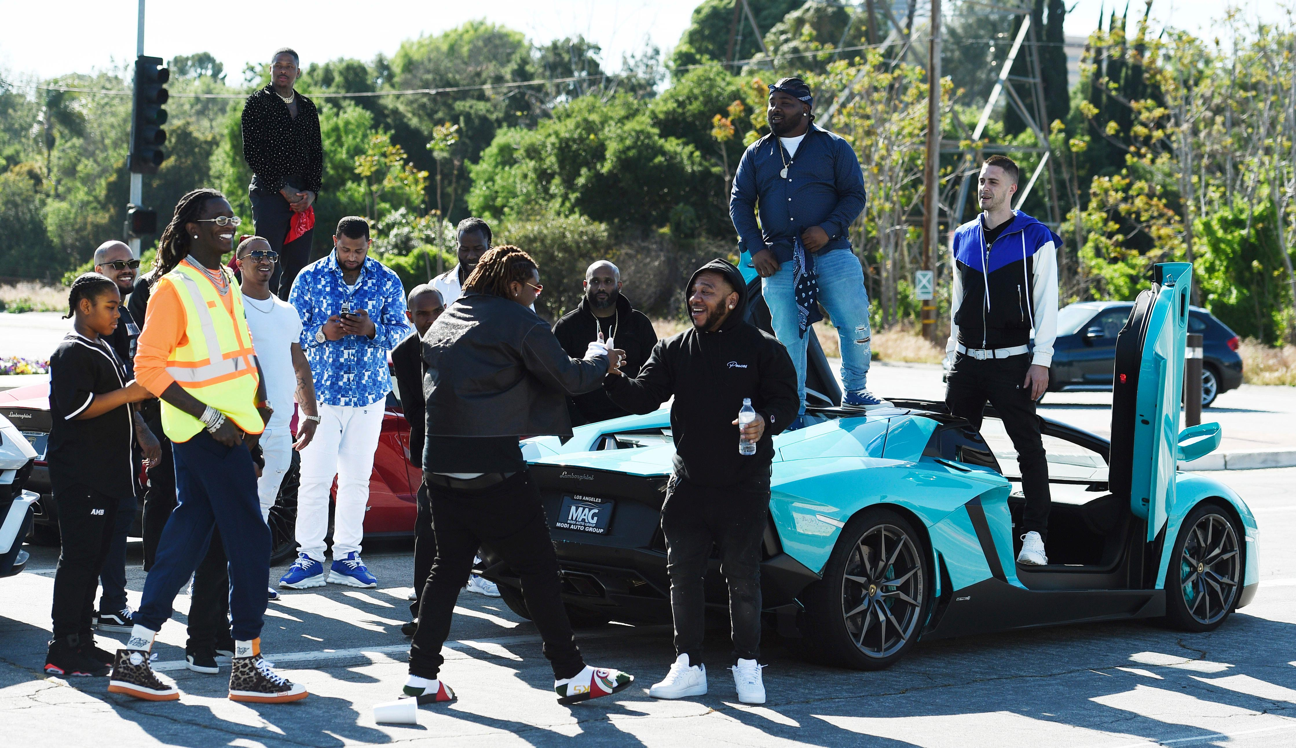 Attendees of a burial service for the late rapper Nipsey Hussle, including rapper YG, upper left holding bandana, gather together outside their cars before leaving Forest Lawn Hollywood Hills cemetery, Friday, April 12, 2019 in Los Angeles. (Photo by Chris Pizzello/Invision/AP)