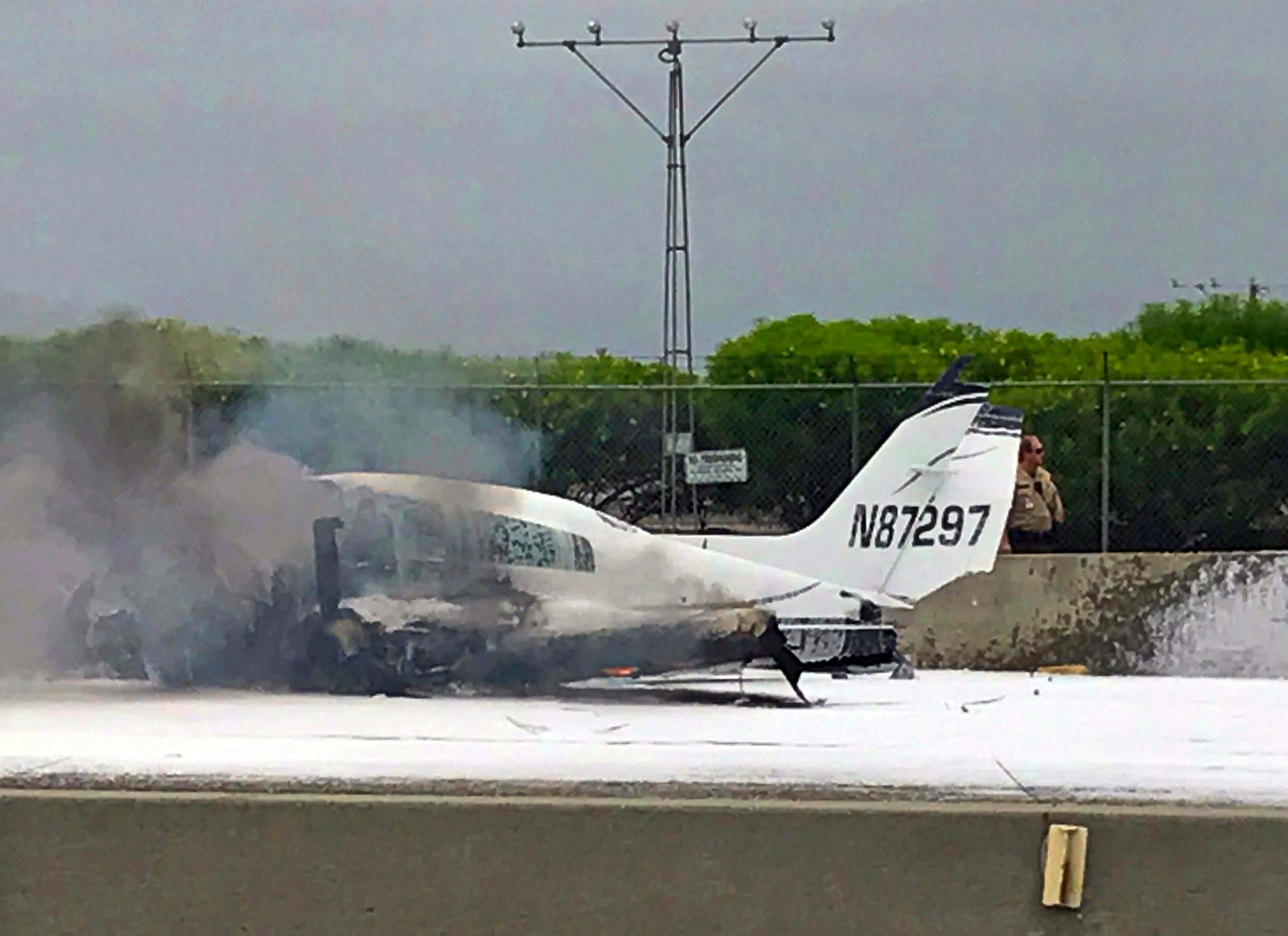 Flame and smoke erupt from a twin-engine prop jet after it crashed on Interstate 405, just short of the runway at John Wayne Orange County Airport, rear, in Costa Mesa, Calif., Friday, June 30, 2017. Officials said two people were injured and were taken by helicopter to a hospital. The freeway was shut down in both directions. (Wendy Haskell via AP)