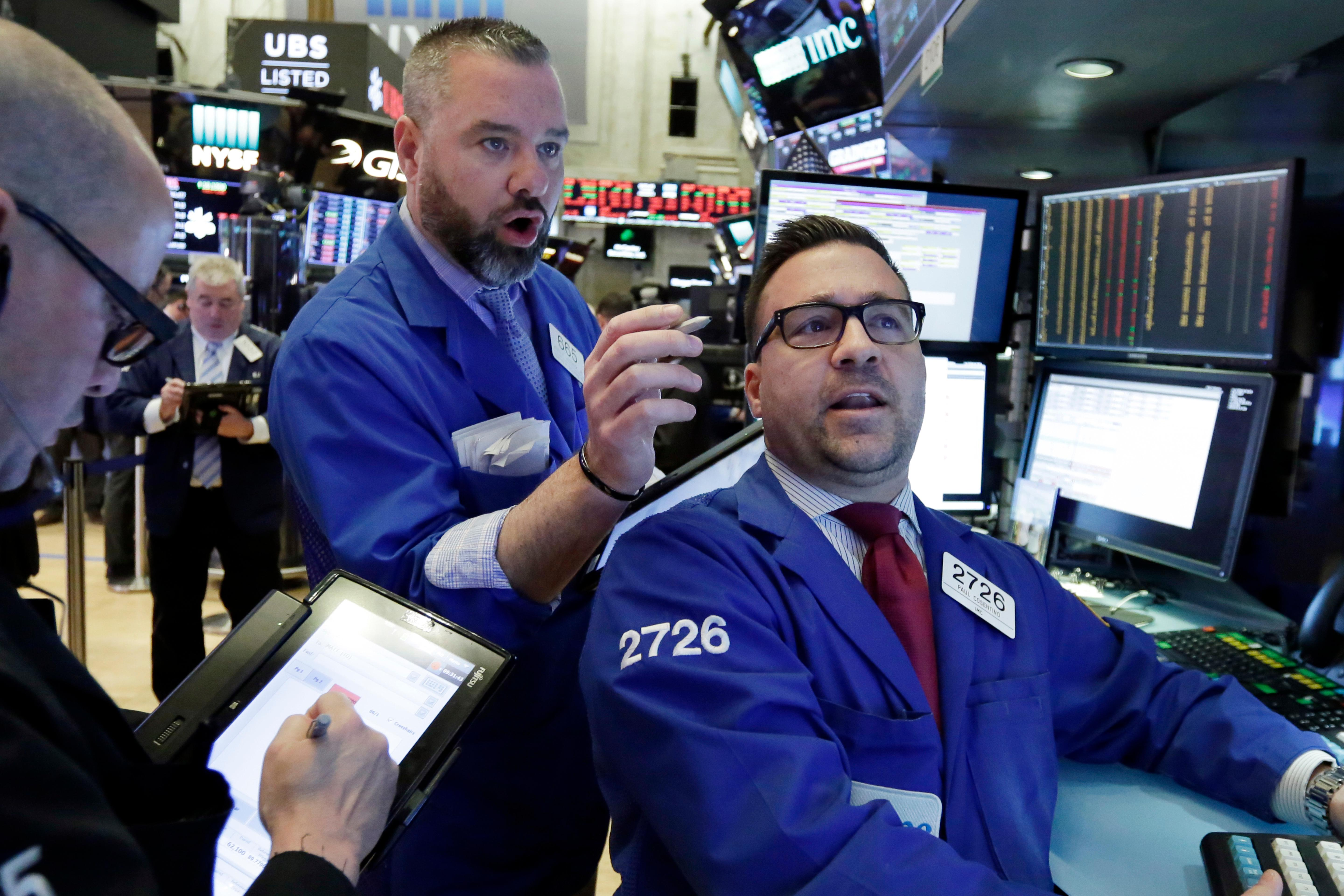 Trader Kevin Lodewick, center, and specialist Paul Cosentino, right, work on the floor of the New York Stock Exchange, Tuesday, Feb. 6, 2018. The Dow Jones industrial average fell as much as 500 points in early trading, bringing the index down 10 percent from the record high it reached on Jan. 26. (AP Photo/Richard Drew)<p></p>