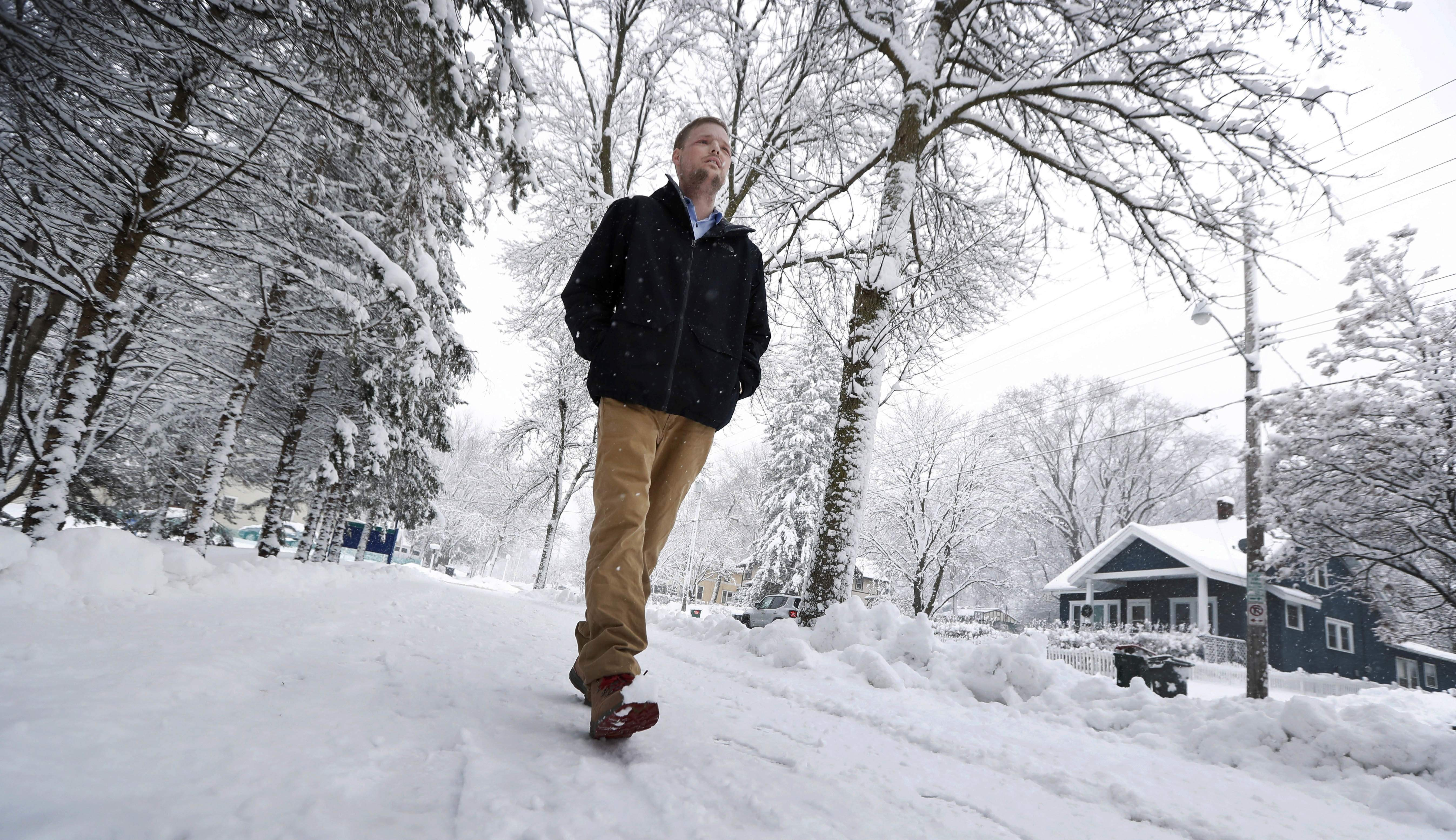 In this Jan. 25, 2017, photo, face transplant recipient Andy Sandness walks to the Saint Marys Hospital campus at Mayo Clinic in Rochester, Minn. Sandness can pinpoint the day he looked normal. About three months after the procedure, he was in an elevator with a little boy who glanced at him, then turned to his mother without appearing scared or saying anything. 'I knew then,' he says, 'that the surgery was a success.' THE ASSOCIATED PRESS