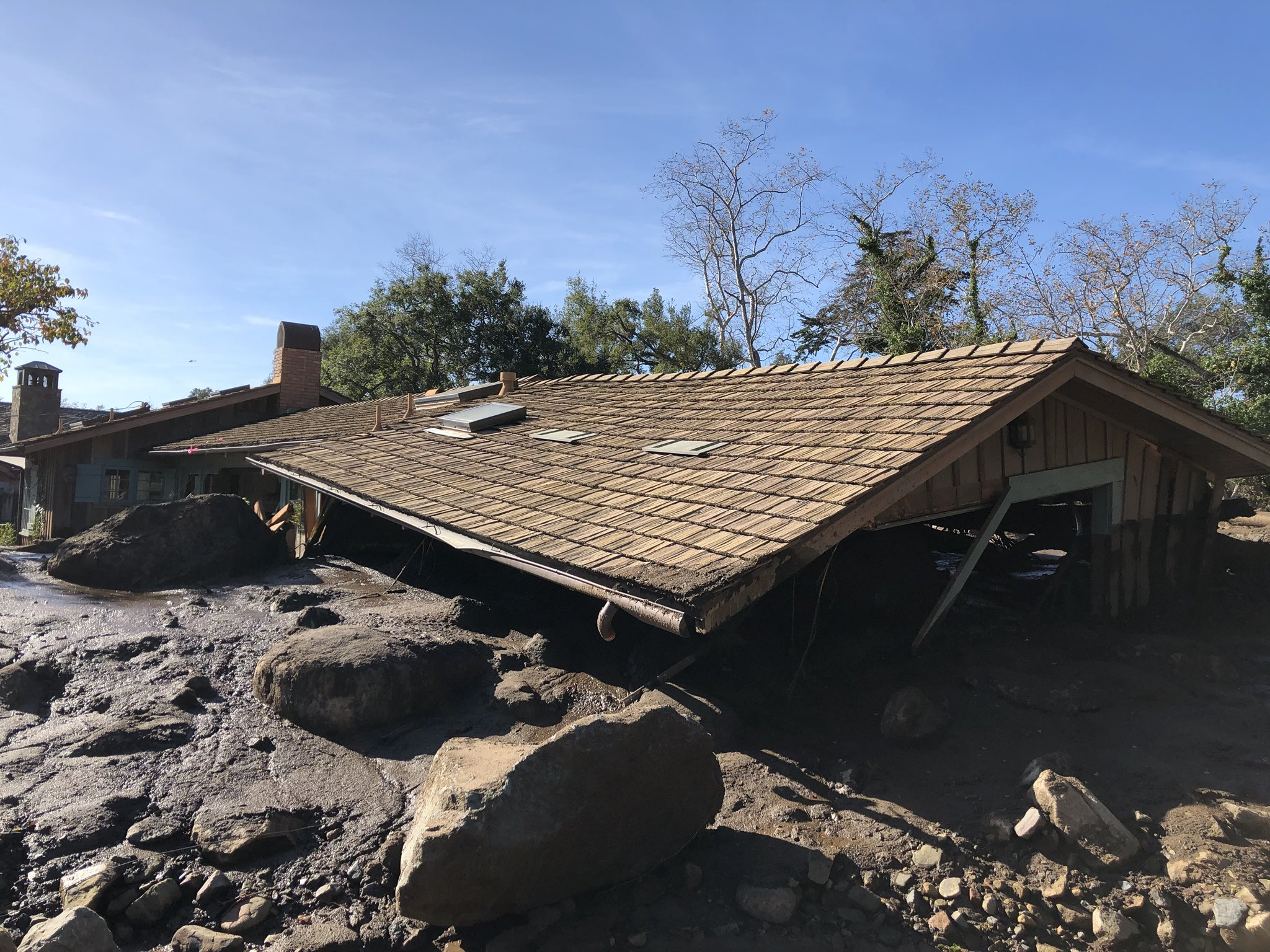 Mudflow, boulders , and debris from heavy rain runoff early Tuesday reached the roof of a single story home off San Ysidro Creek in Montecito. (Photo & Caption: Mike Eliason, Santa Barbara County Fire Dept.)