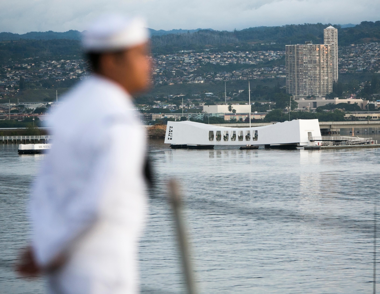 A Navy sailor is seen as the Arleigh Burke-class guided-missile destroyer, the USS Halsey, passes the USS Arizona Memorial, Wednesday, Dec. 7, 2016, in Honolulu. Today marks the 75th anniversary of the surprise Japanese attack on Pearl Harbor initiating the War in the Pacific. (AP Photo/Marco Garcia)