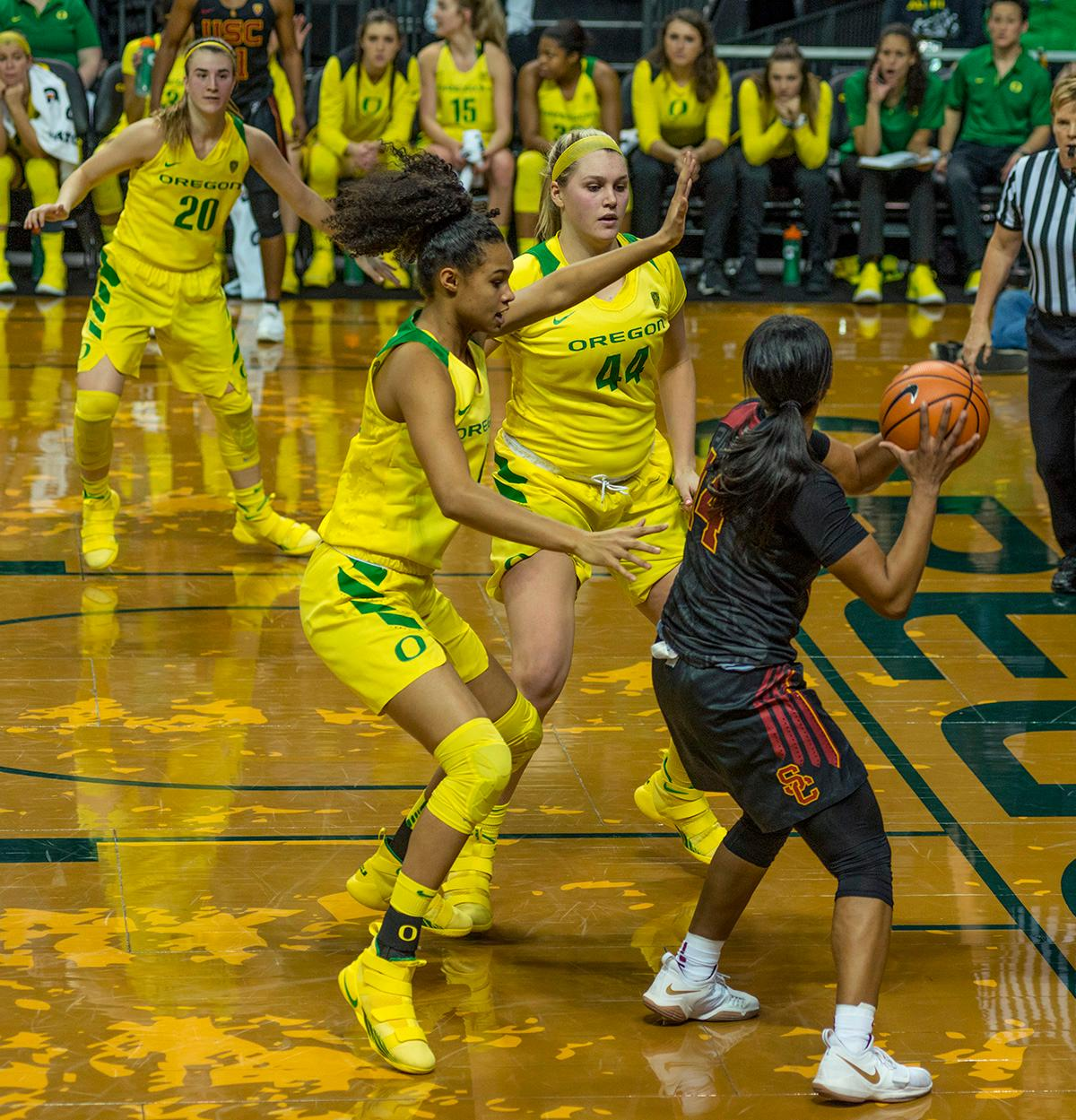 Oregon Ducks Satou Sabally (#0, left) and Mallory McGwire (#44) close in on USC Trojans Sadie Edwards (#14). The Oregon Ducks defeated the USC Trojans 80-74 on Friday at Matthew Knight Arena in a game that went into double overtime. Lexi Bando sealed the Ducks' victory by scoring a three-pointer in the closing of the game. Ruthy Hebard set a new NCAA record of 30 consecutive field goals over three games, the old record being 28. Ruthy Hebard got a double-double with 27 points and 10 rebounds, Mallory McGwire also had 10 rebounds. The Ducks had four players in double digits: Ruthy Hebard with 27; Maite Cazorla with 17; Sabrina Ionescu with 15; and Lexi Bando with 11. The Ducks are now 24-4, 13-2 in the Pac-12, and are tied for first with Stanford. Photo by Dan Morrison, Oregon News Lab