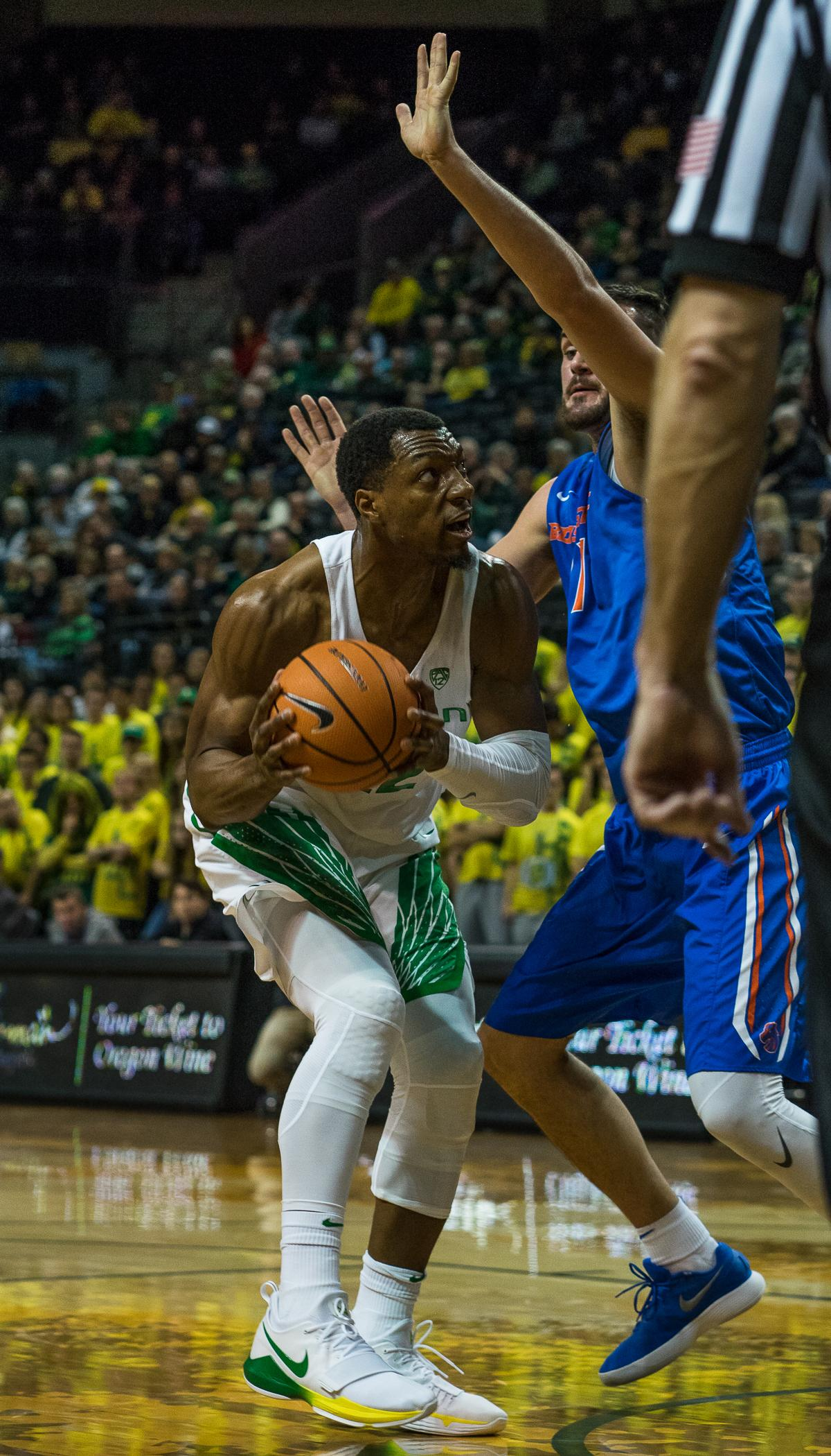 The University of Oregon's MiKyle McIntosh (#22) looks for an opening in Boise State Bronco Zach Haney's (#11) defense. The Boise State Broncos defeated the University of Oregon Ducks 73 – 70 at Matthew Knight Arena in Eugene, Ore., on December 1, 2017. Photo by Kit MacAvoy, Oregon News Lab
